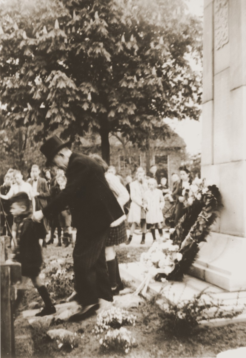 Wearing a formal jacket and top hat, Louis Meijer places a wreath at the monument for local victims of the Second World War during a memorial ceremony in Boekelo.  Walking in front of Meijer is his orphaned grand nephew, Rene Gruneberg.