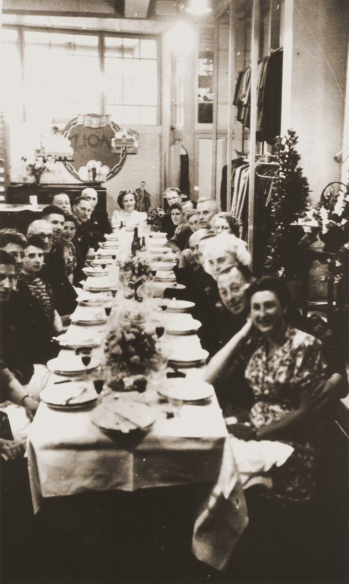 Festive dinner celebrating the reopening of the Zion family business at the store in Eibergen.  Among those pictured are Bep Meijer (front, right side) and Julius Zion (fifth from the front on the left side).  From August 1942, when it was confiscated, until April 1945, the Zion clothing and fabric store had been used by the Germans as a military warehouse and barracks.