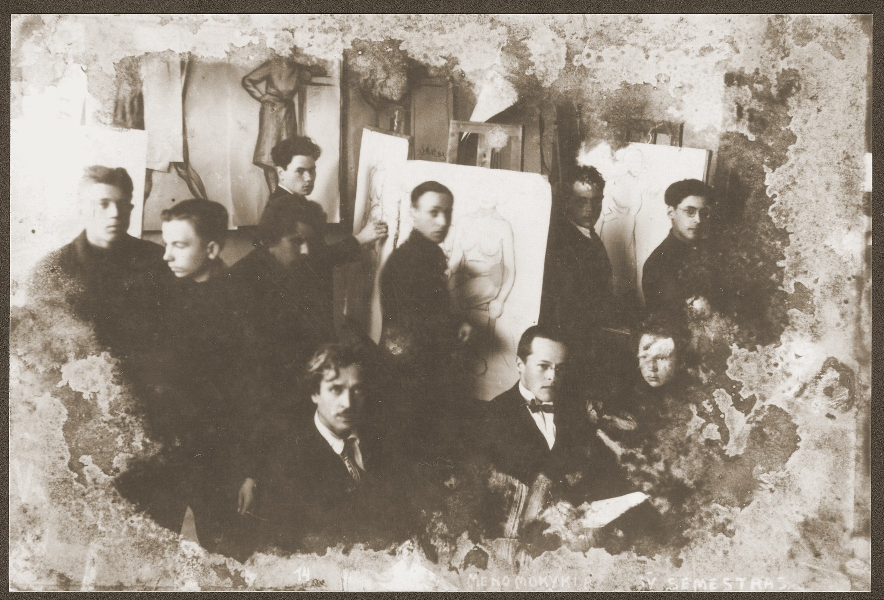 Damaged photograph of a class at the Kaunas Art Institute that survived the destruction of the Kovno ghetto.  Among those pictured is the artist Jacob Lifschitz (at the easel on the far left).  The photograph was buried with the artist's drawings shortly before the liquidation of the ghetto, and retrieved by his wife after the liberation.