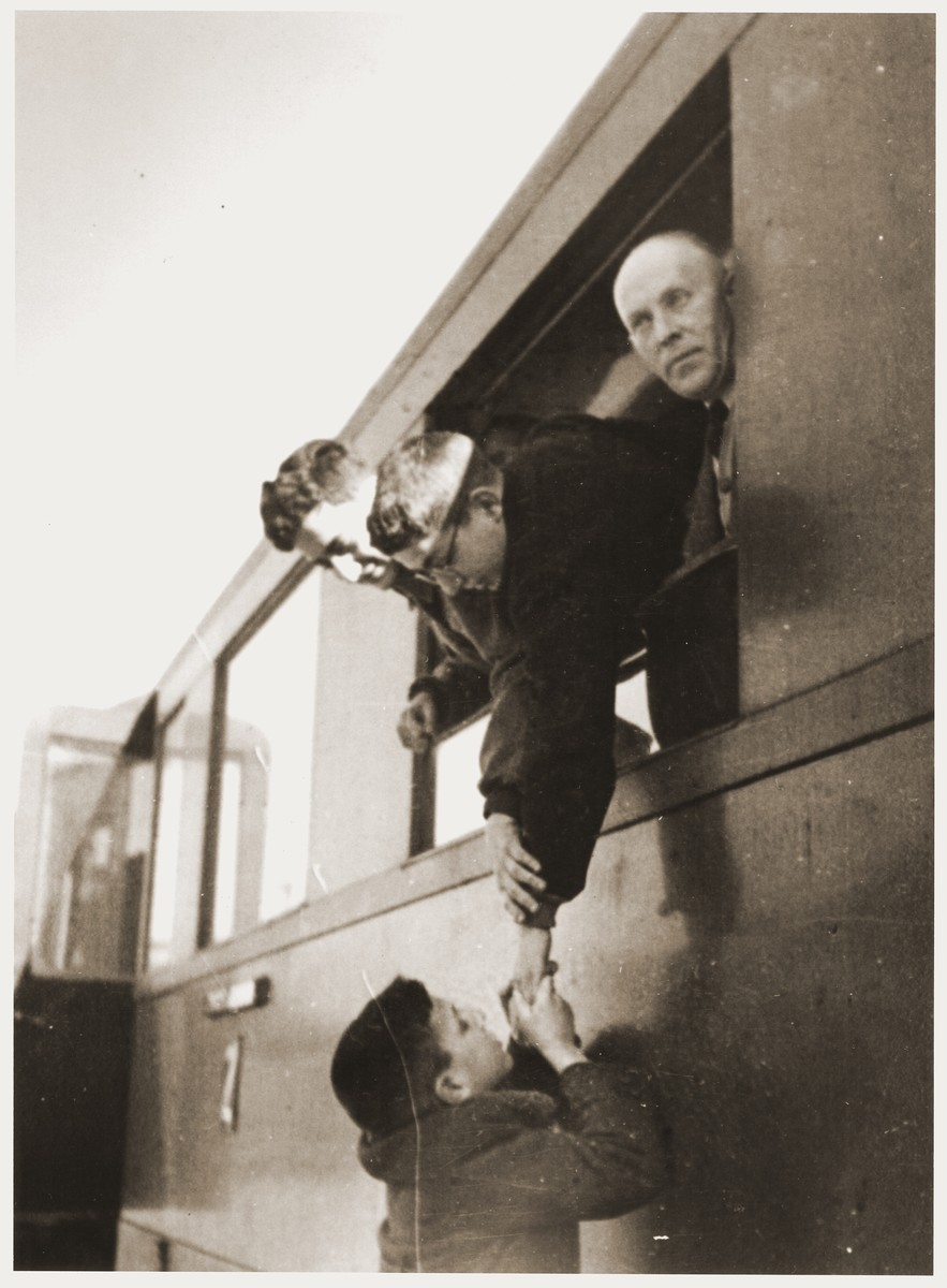 Shmuel Rabinovitch kisses his older brothers, Amos and Binyamin, farewell as they leave for Palestine from the Vilna train station.