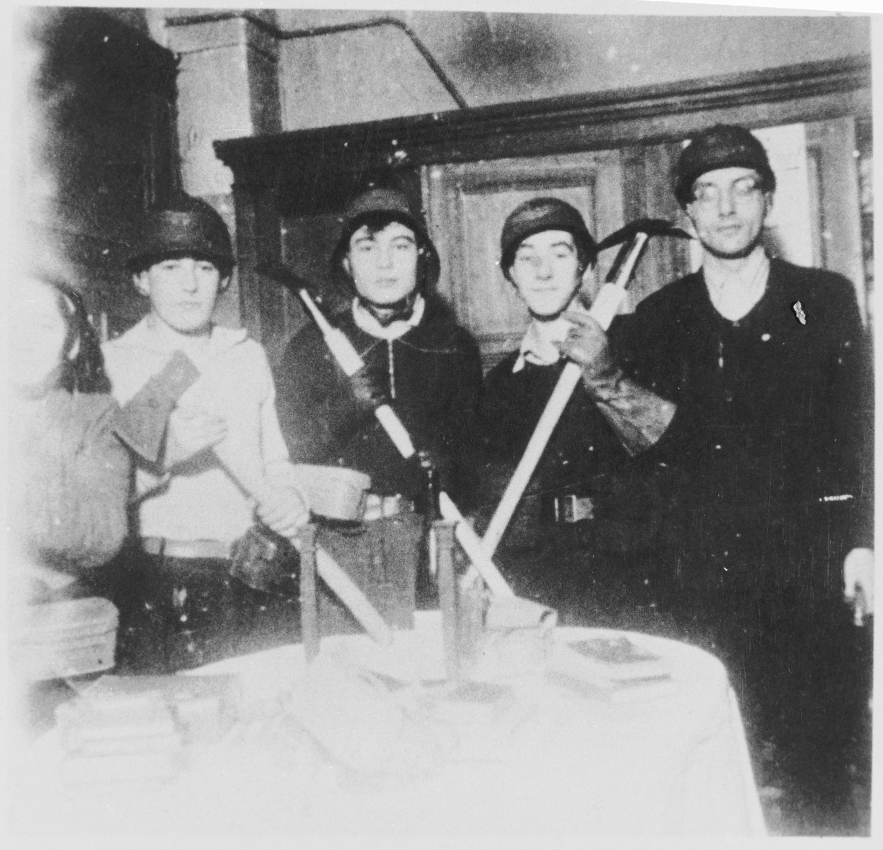 Students and teachers at the Youth Aliyah school in Berlin pose with helmets and tools during a mandatory air raid patrol shift.    Pictured on the far right is the director of the school, Jizchak Schwersenz.