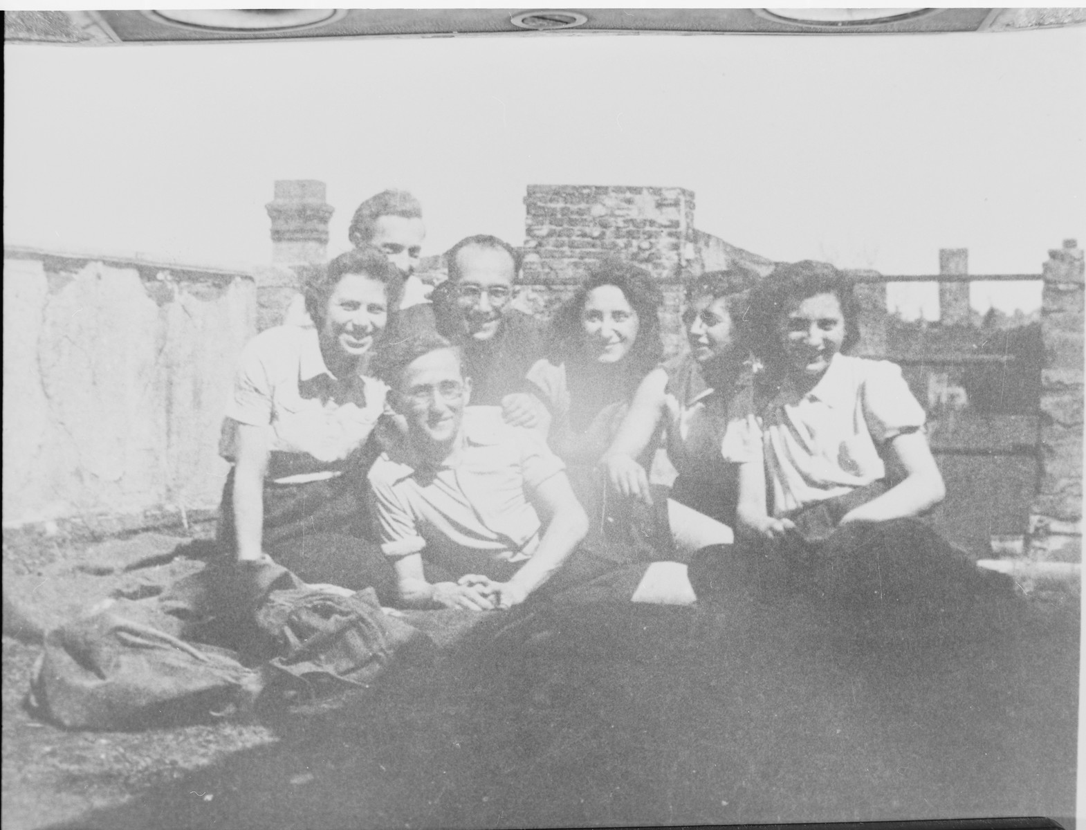 Group portrait of Zionist youth on the roof top of the Youth Aliyah school on Artillerie Strasse 14 in Berlin (where the school was relocated after the original building was damaged by a bomb).    Pictured from left to right are: Lotte Kaiser, Schlomo Lewin and Jizchak Schwersenz.  Gad Beck is reclining in the foreground.