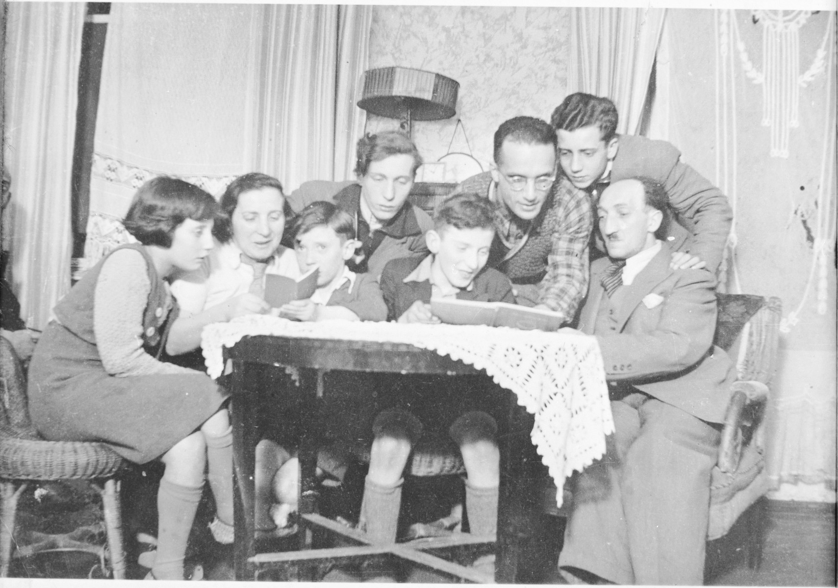 Jizchak Schwersenz studies a book with members of the Lewin family in their home in Berlin.  Pictured from right to left are: Arthur Lewin (father), Manfred Lewin, Jizchak Schwersenz, Rudolf, Schlomo, Gerd, Jenny (mother), and Caecilie Lewin.