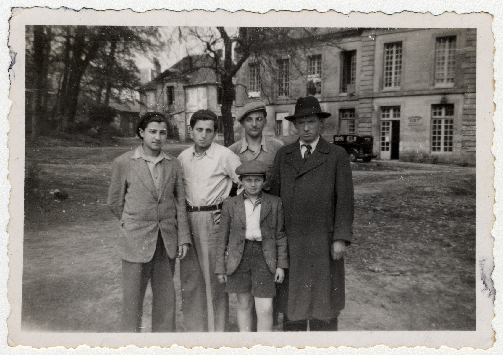 A group of teenagers stand with a child and man outside a home in Saint Pierre de Chartreuse.