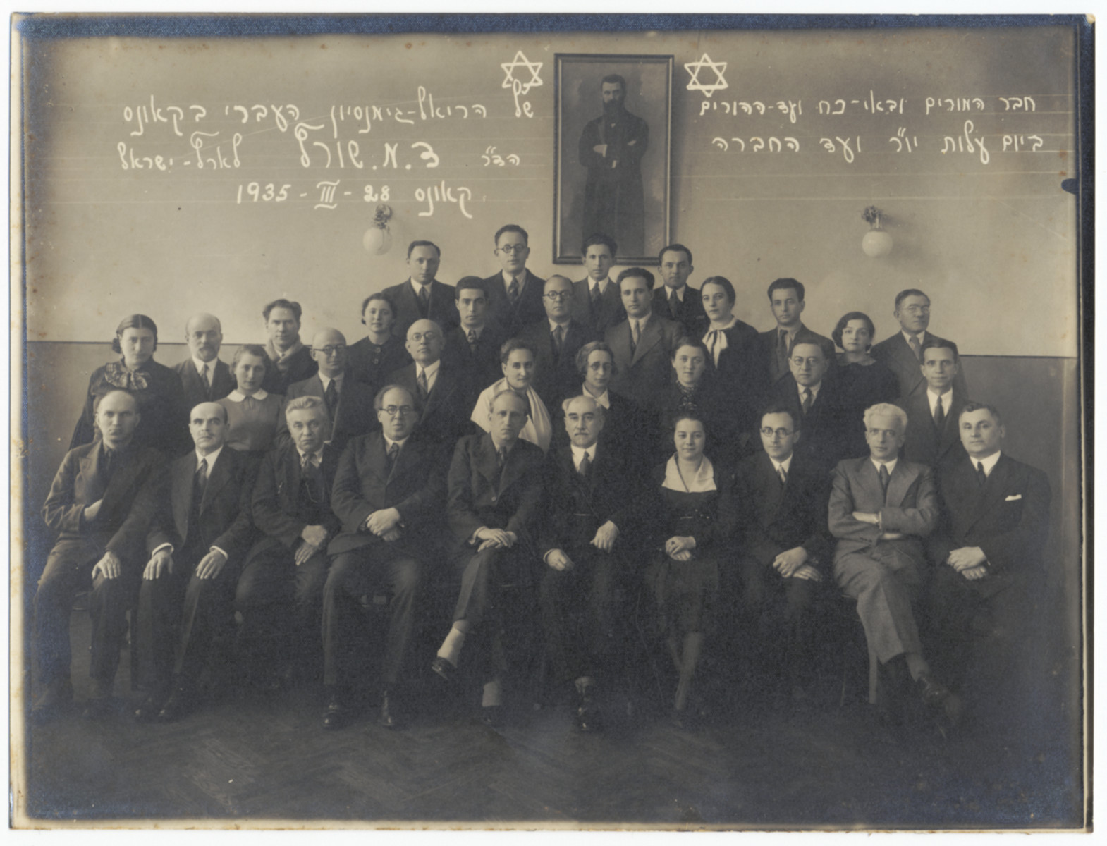 Group portrait of the faculty and board members of the Real Gymnasium in Kaunas.  Among those pictured are Leo Aryeh Zeidel (first row, second from the right) who was a representative of the parents' committee.  Second row: Yavetz (the gym teacher, far right); Mrs. Miller (third from the right).  Third row: Dr. Kissim (the science teacher who died in Dachau, far right), Lena Rachmilevitch (second from right).  Also, Dr. Swartz, Dr. Feldstein (the director of the school), Natan Greenblat and Dr. Junblanski.