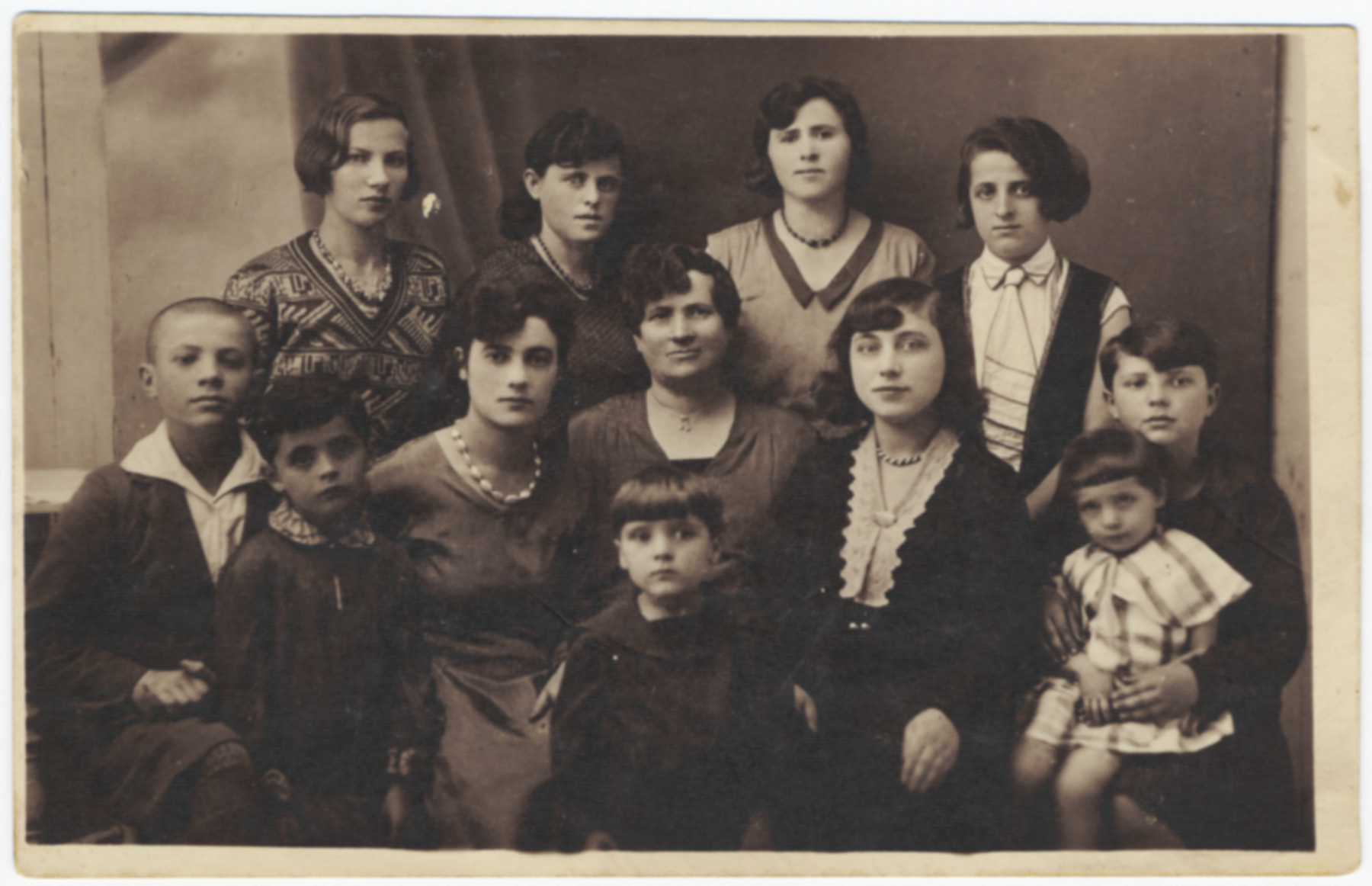 Studio portrait of an extended prewar Jewish family in Poland taken at a wedding.   Pictured are members of the Beker family.  Only two of those pictured suvived: Haya Beker Kleinhandler is in the middle (She is the oldest sister of Manya's mother).  Manya Moskowicz is standing on in the front, second from the left.  (Her mother is not pictured since she was pregnant with her youngest child.)