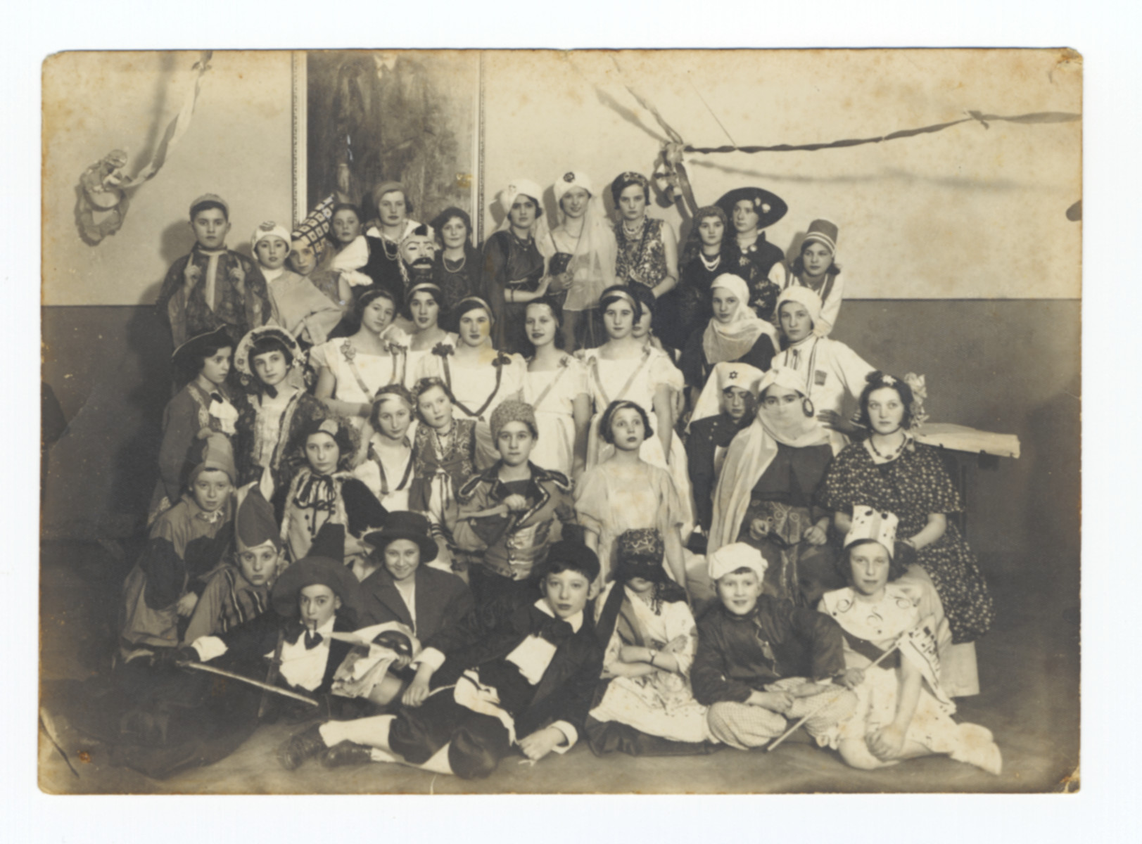 Group portrait of Jewish children wearing costumes at a Purim Ball in Kaunas.  Pictured in the front is Alexander Zeidel dressed as a Hassid.