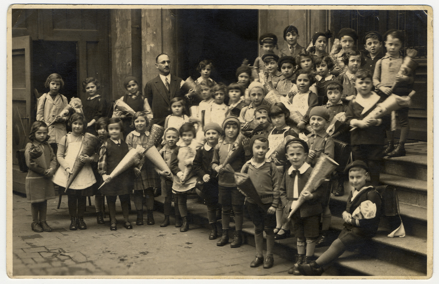 Group portrait of a first grade class holding cones of sweets in a religious elementary school which met in the synagogue in Nuremberg, Germany.  Among those pictured is Meir Schwarz, top row, second from the left.