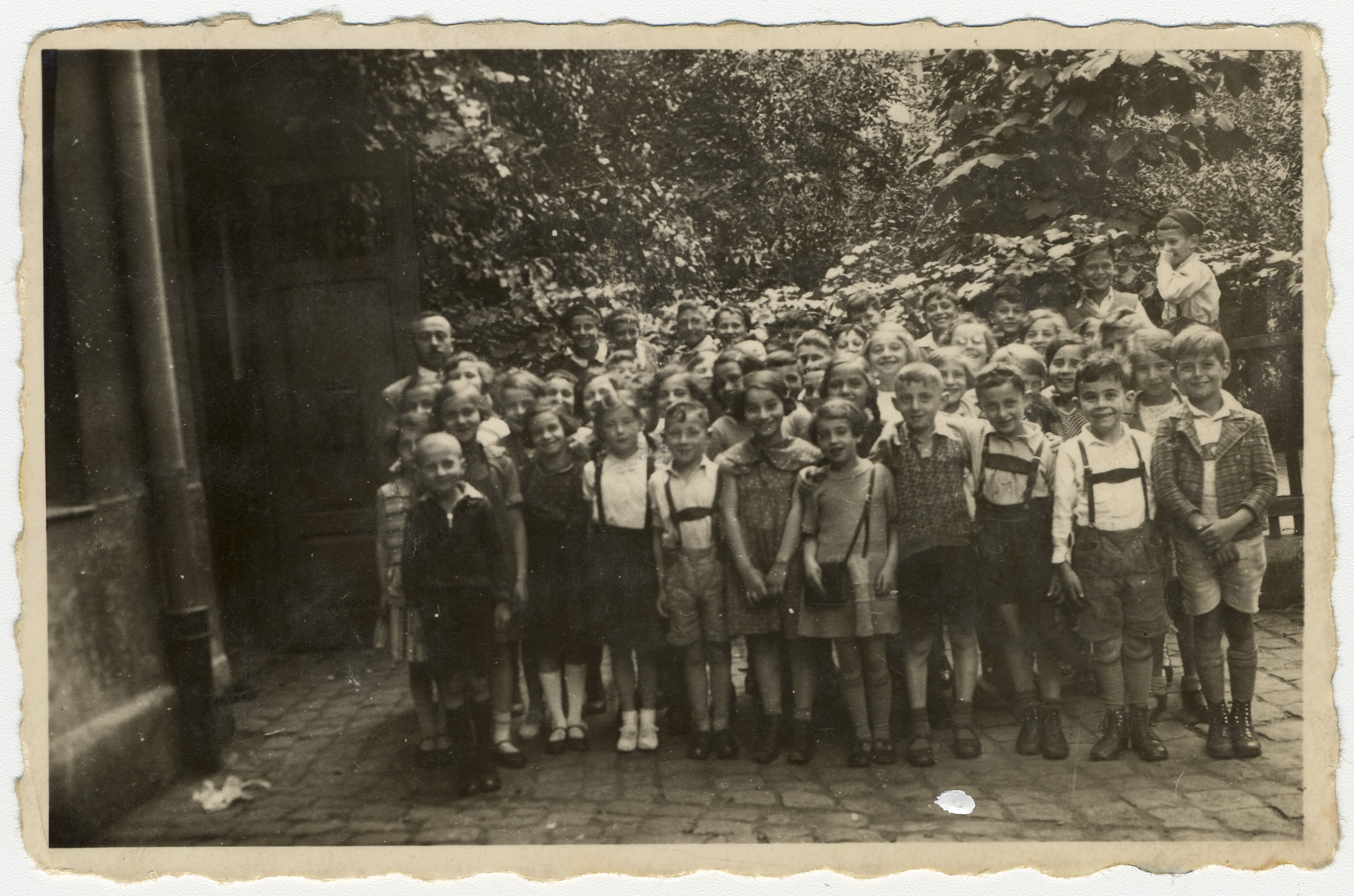 Group portrait of a second grade class in a religious elementary school in Nuremberg, Germany.  Among those pictured is Meir Schwarz, front row, fourth from the left.  Standing behind him is the teacher Mr. Blum.