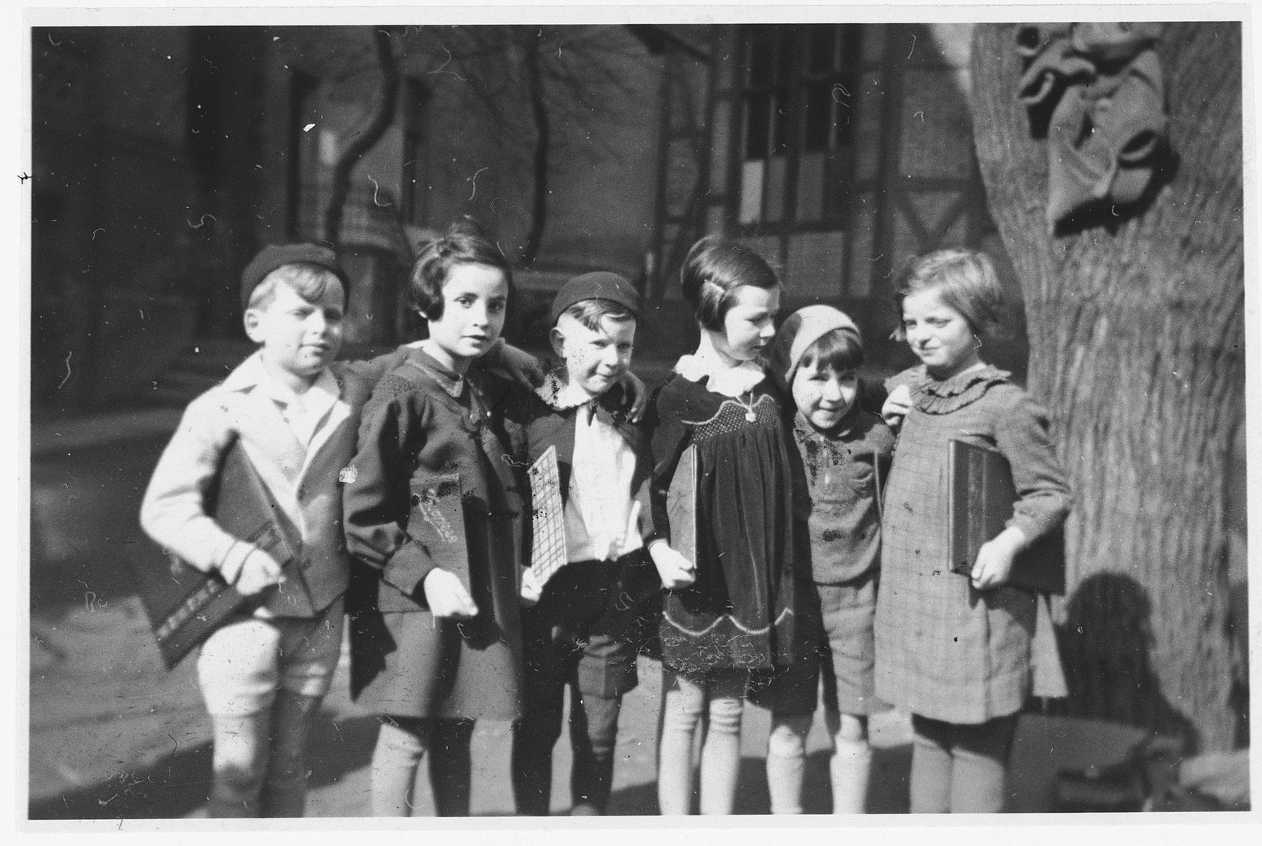 Six school friends pose in a row with their report cards after completing first-grade.   Those pictured include Hannelore Mansbacher (first from right), Heinz Kleczewski (second from right) and Hanna Frischer (second from left). Only Hannelore Mansbacher survived the war.