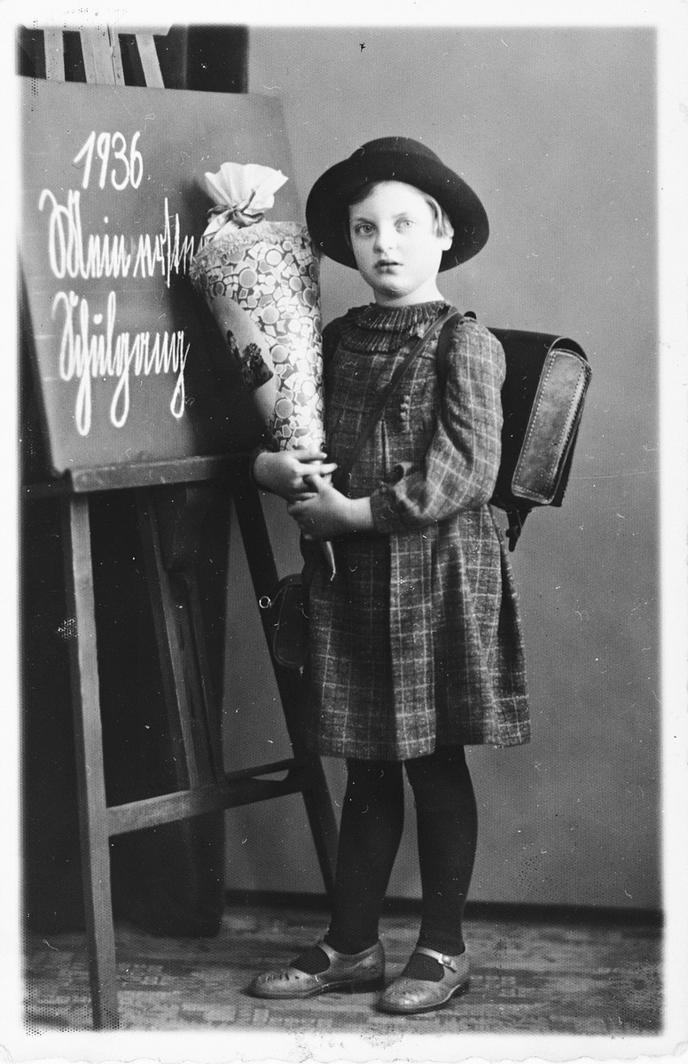 "Hannelore Mansbacher on her first day of school holding a container of candy and standing near a blackboard with the caption ""1936 Mein erster Schultag"" (1936 my first school day)."