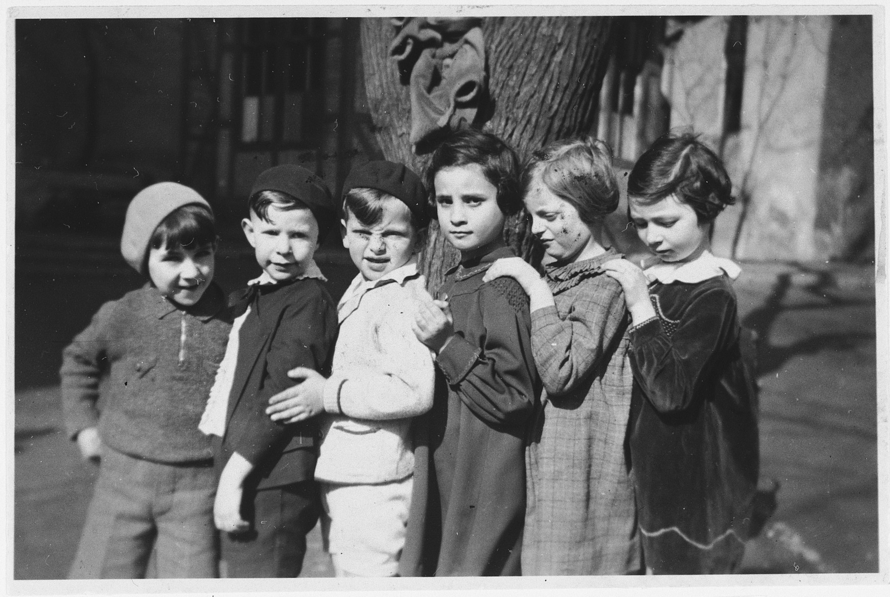 Six school friends pose in a line after the completion of first-grade.   Those pictured include Hannelore Mansbacher (second from right), Heinz Kleczewski (first from left) and Hanna Frischer (third from right). Only Hannelore Mansbacher survived the war.
