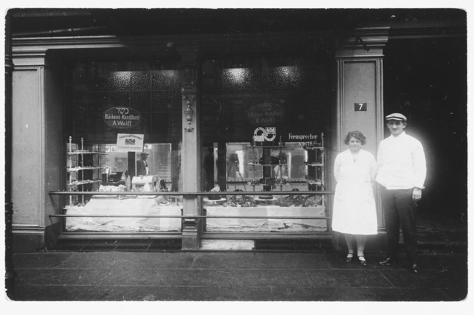 Proprietors of a kosher bakery stand in front of their store window.  Pictured are Angela Stiefel and her brother-in-law Adolf Wolf.