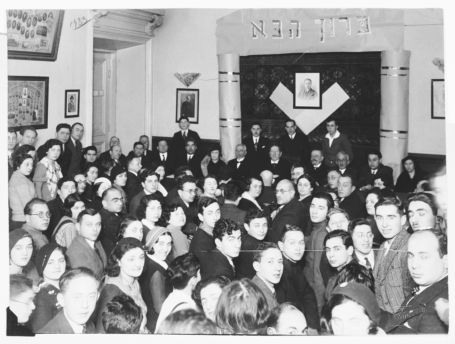Jewish faculty and students of the Hebrew gymnasium in Vilna are gathered in the auditorium of the school during the visit of Zionist leader Nahum Sokolow.  Among those pictured is Ralph Denishevsky (beneath the Hebrew welcome sign, second from the right).
