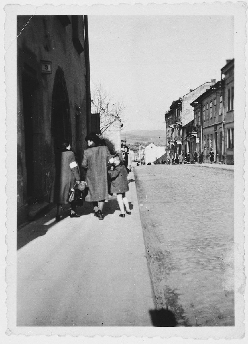 Polish Jews wearing armbands walk down a street of the [Nowy Sacz] ghetto.