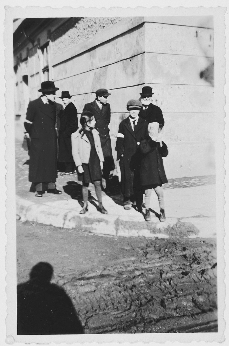 Polish Jews wearing armbands walk down a street of the [possibly Nowy Sacz] ghetto.