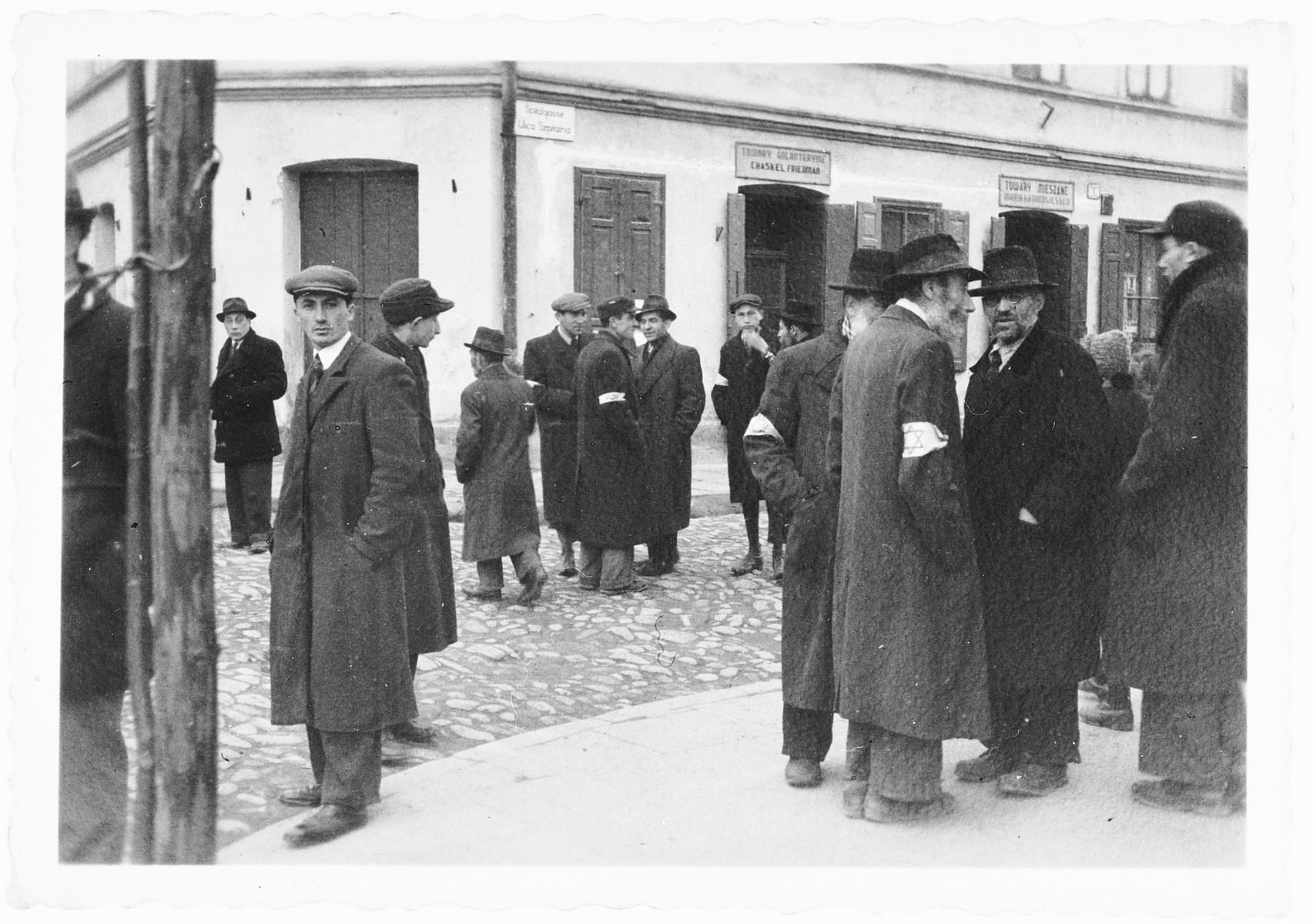 Polish Jews stand on a street corner of the [possibly Nowy Sacz] ghetto.