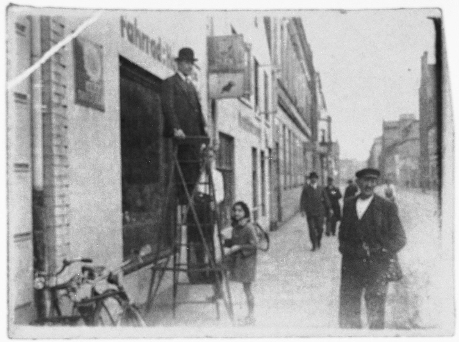 Josef Zwienicki stands on a ladder outside his bicycle store in Bremen.  Below him is his daughter Liesel.  To her left is a German customer who later collaborated in the murder of his wife.