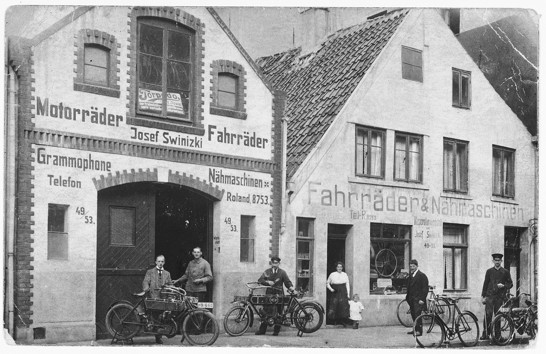 Josef Zwienicki stands in front of his bicycle shop amid several customers.