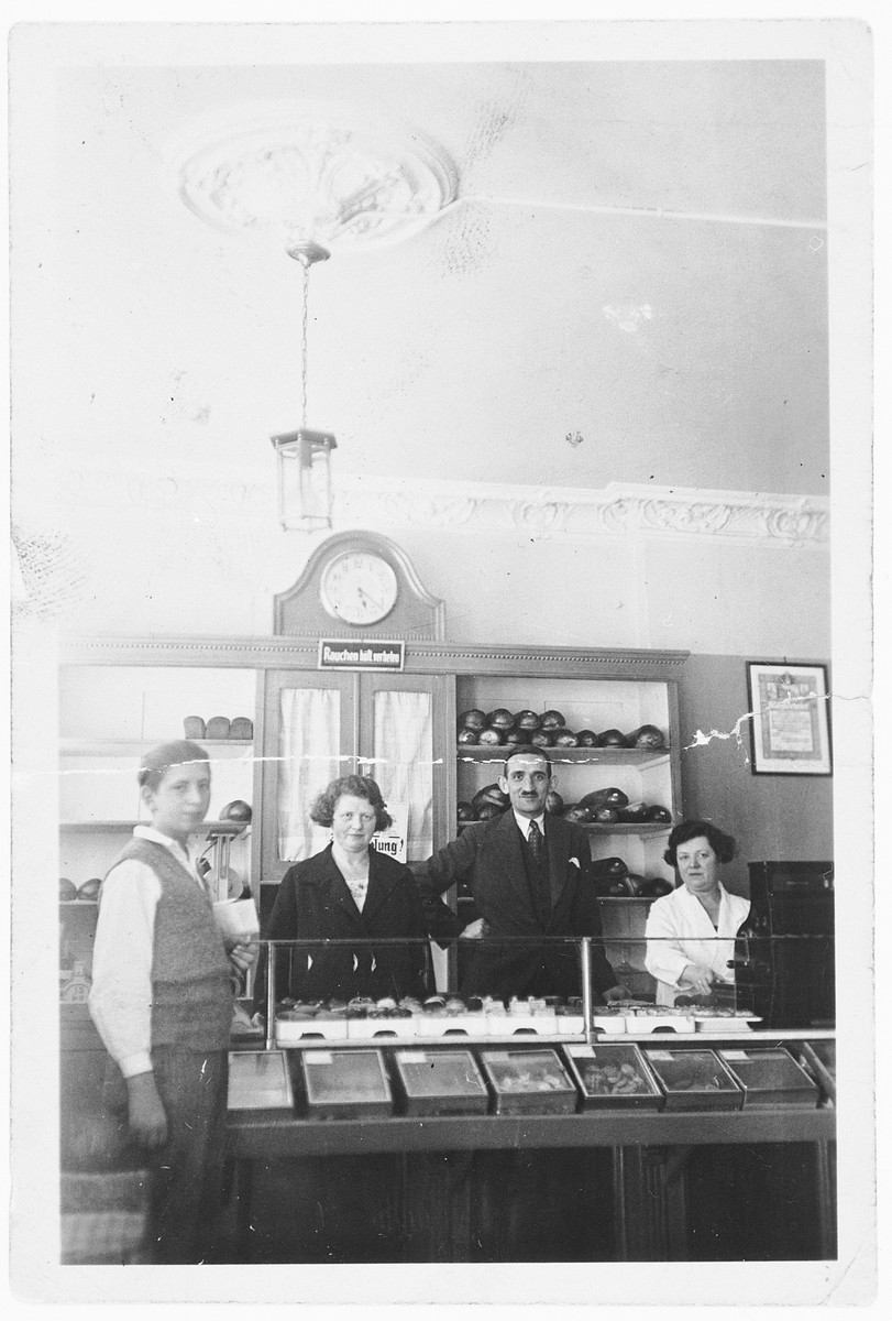 Proprietors of a kosher bakery stand next to a display counter in Hamburg.  In the center are the owners, Marta and Adolf Wolf (aunt and uncle of the donor) and Marta's sister, Angela.