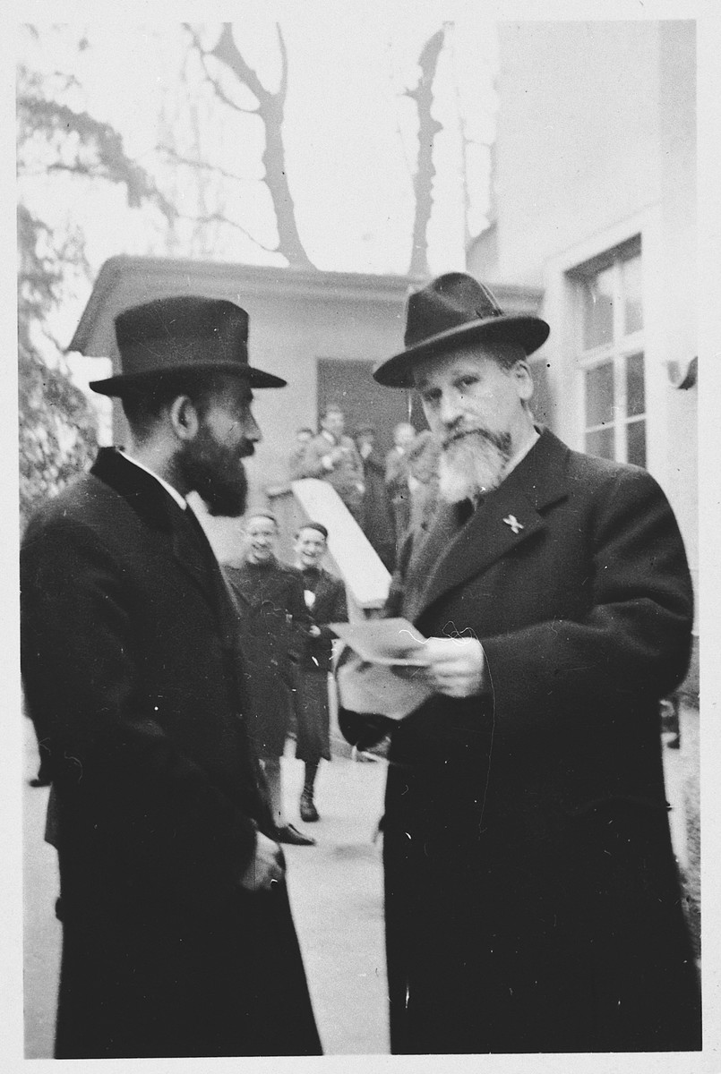 Two rabbis hold a conversation outside the Breuer Yeshiva in Frankfurt.  Dr. Posen, a dayan or religious judge and a teacher at the yeshiva is on the left.  Dr. Moses Breuer, brother of the head of the yeshiva, is on the right.