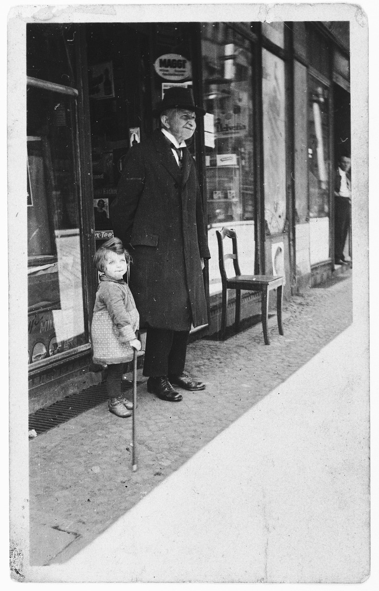 Hannelore Mansbacher with her grandfather Samuel Moses (mother's father) in front of her parents' grocery store.