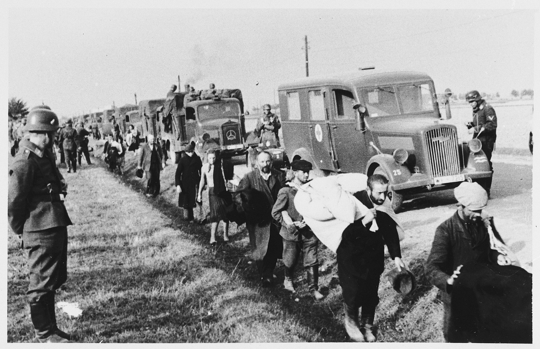 German troops supervise a column of [probably Polish Jews] marching by the side of a road in a forced resettlement action.