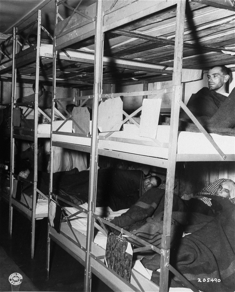 Survivors lie in multi-tiered bunks in the infirmary in the Dachau concentration camp soon after its liberation.
