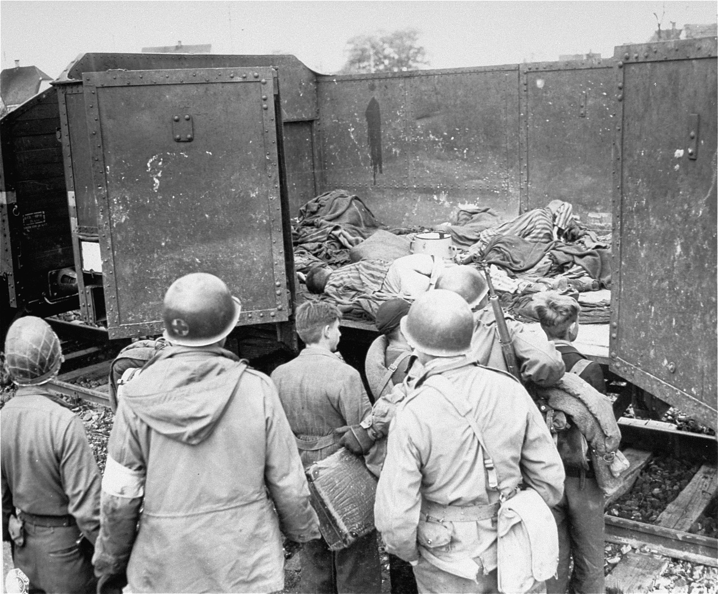 "American soldiers of the U.S. 7th Army, force boys believed to be Hitler youth, to examine boxcars containing bodies of prisoners starved to death by the SS.   Original caption reads:  ""Seventh U.S. Army soldiers force these young Germans, believed to be members of the Hitler Youth movement, to view roofless freight cars filled with the bodies of victims of Nazi atrocities who died en route to Dachau.  Many German boys have been caught acting as snipers against U.S. troops in Germany."""