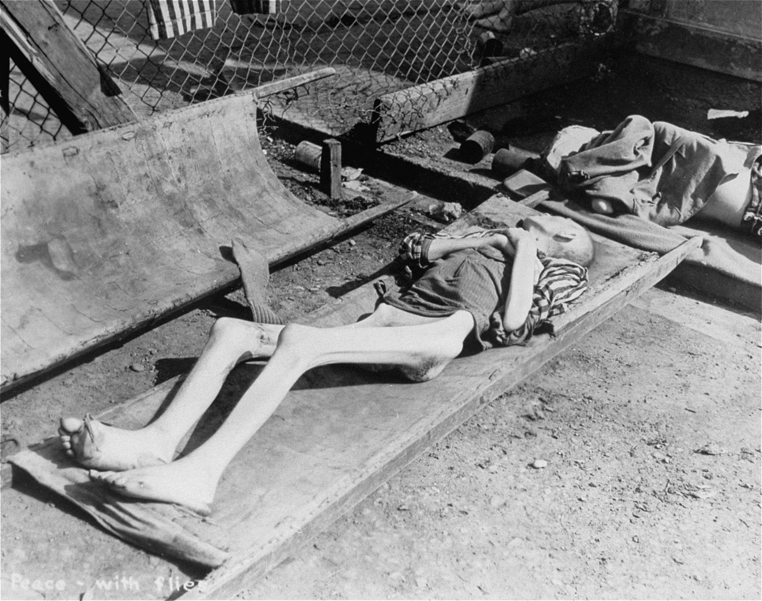 The emaciated, partially-clothed corpse of an inmate at the Dachau concentration camp lies outside on a stretcher awaiting removal for burial.