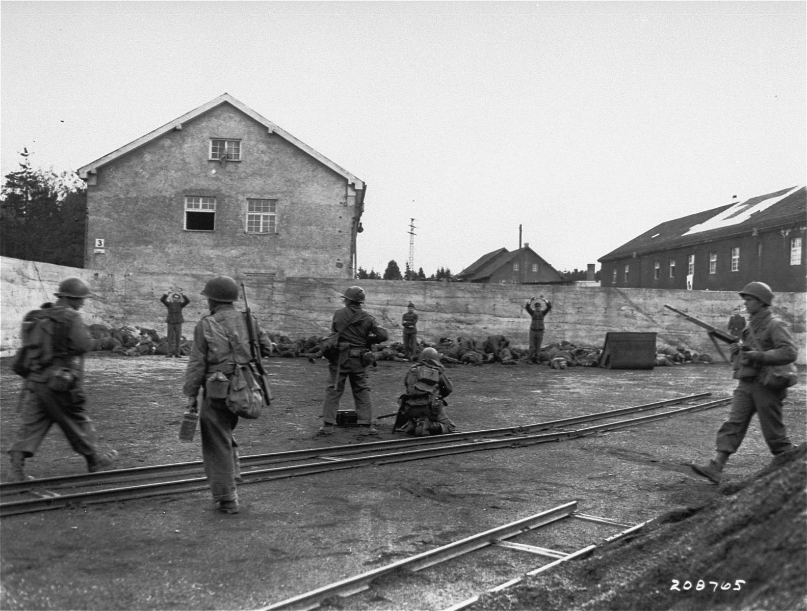 American soldiers execute SS camp guards who have been lined up against a wall during the liberation of the Dachau concentration camp.  Among those pictured is Pfc. John Lee (far right).
