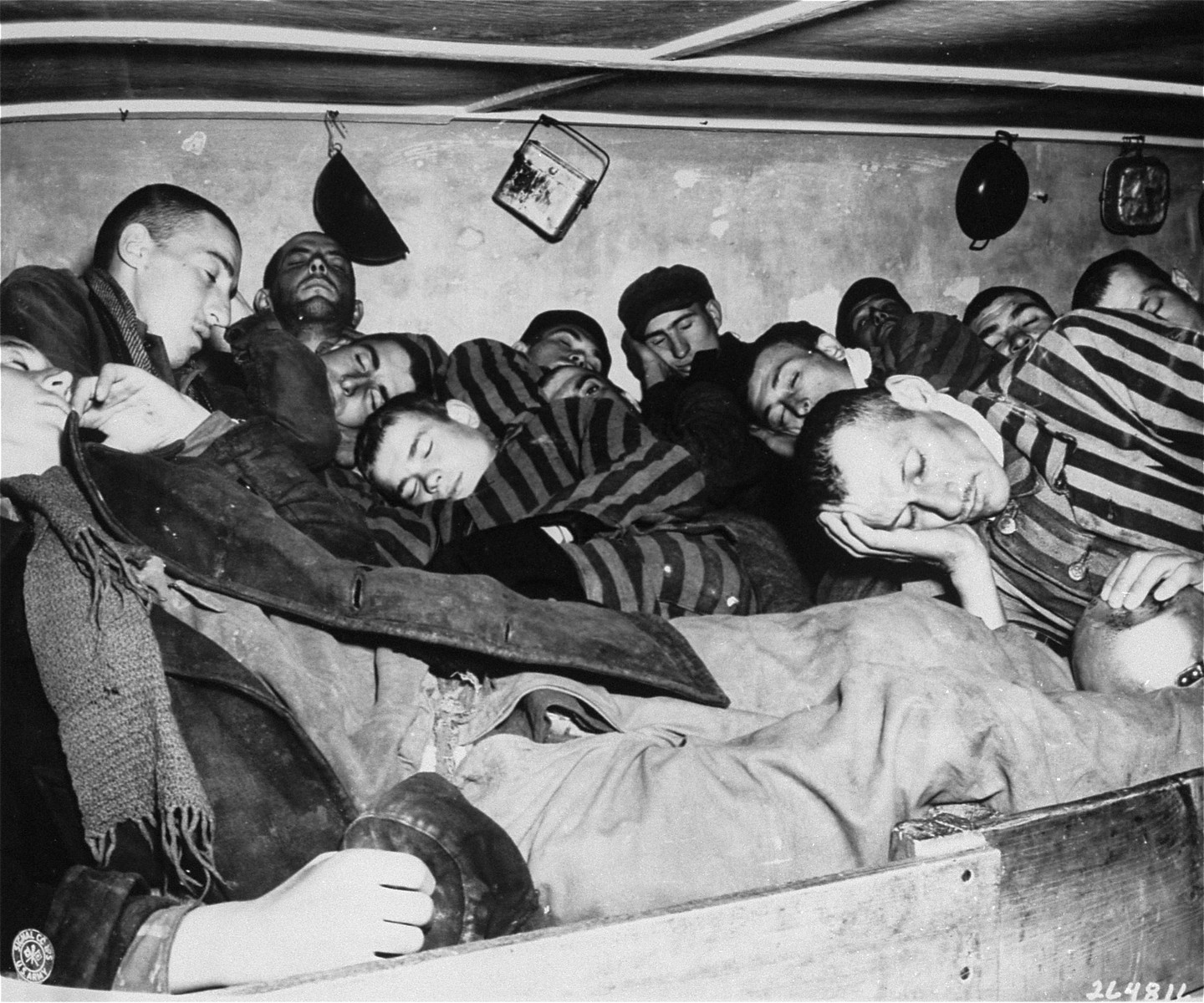 Survivors in Dachau packed into overcrowded sleeping quarters, where 7 men had to share 2 small beds. The bunks were three-tiered, and anywhere from 350 to 800 men slept in a room crowded with 120 beds.