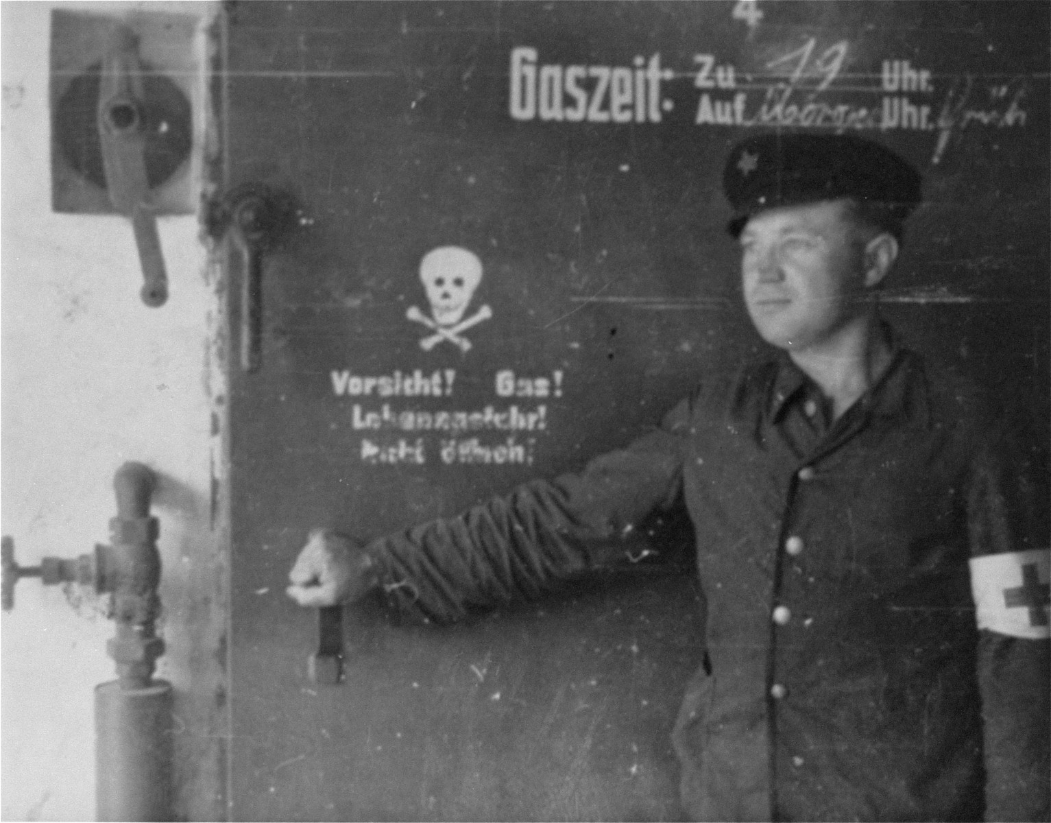 A survivor, probably Yugoslavian due to the red star on his cap, stands by the door of the Gas chamber in Dachau.