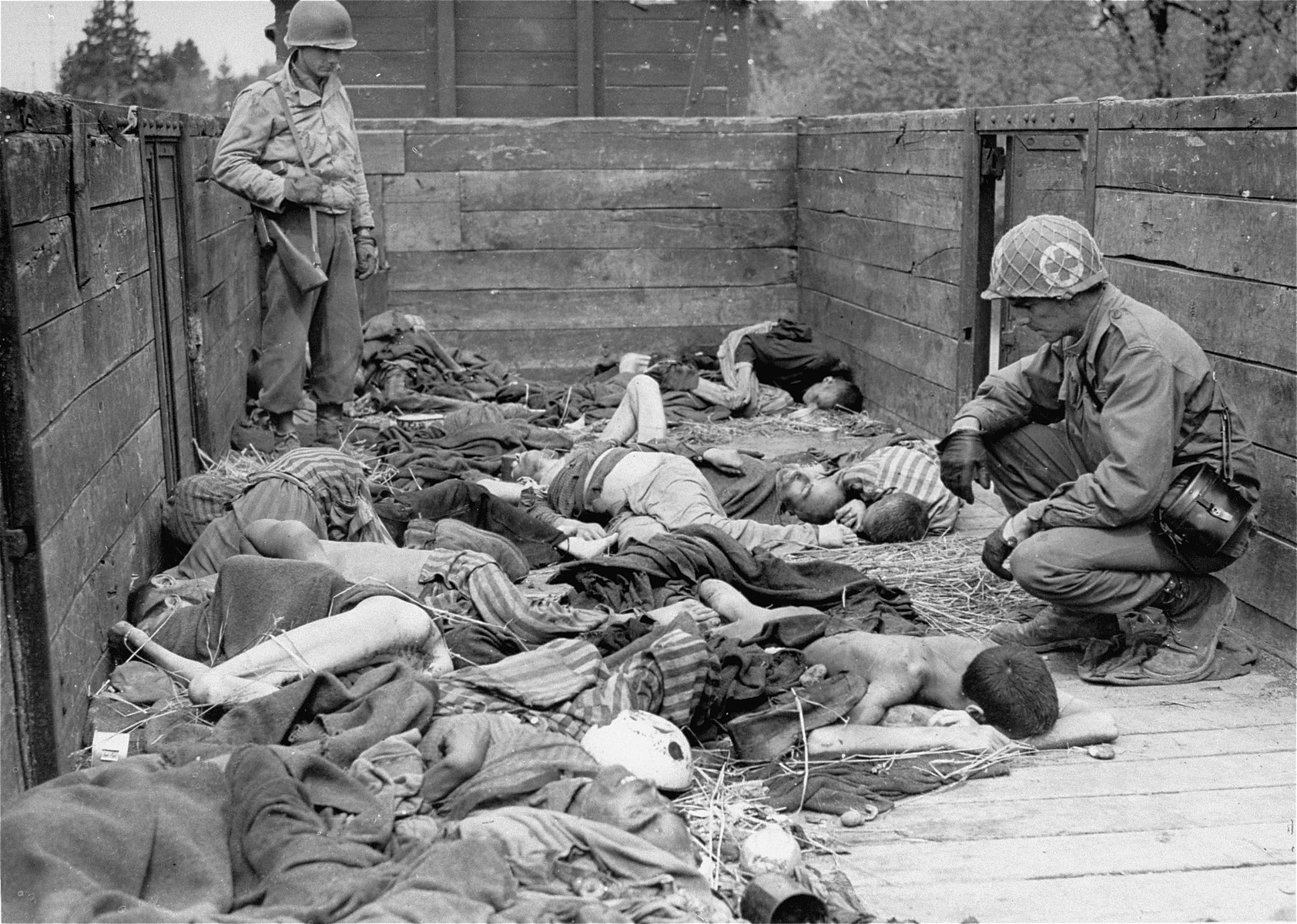 Medical corpsmen of the Seventh US Army view the bodies in one of the open railcars of the Dachau death train.  The soldier standing in the rear of the car is Kenneth Dean Johnston.