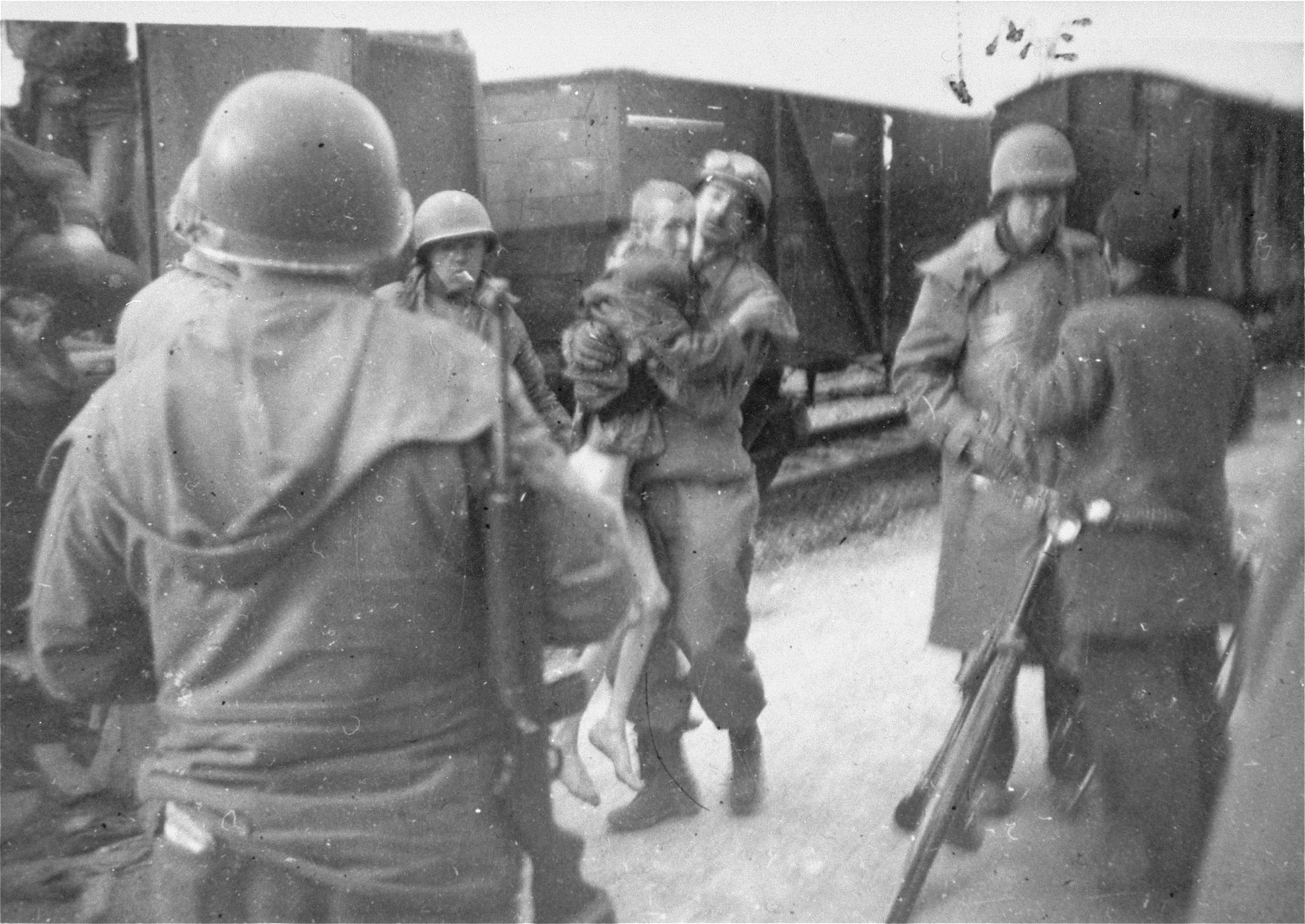 American soldiers remove one of the few survivors from the Dachau death train.  Pictured carrying the survivor is T/4 Sgt. Tony Cardinale and Lieutenant Gerald C. Caskey can be seen speaking to the armed man on the right.