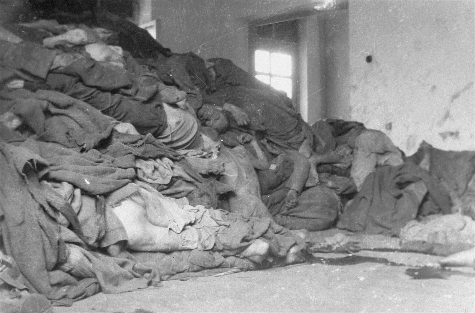 Corpses piled in the crematorium mortuary.  These rooms became so full of bodies that the SS staff and survivors began piling corpses behind the crematorium, where they were found by U.S. troops during the liberation of the camp.