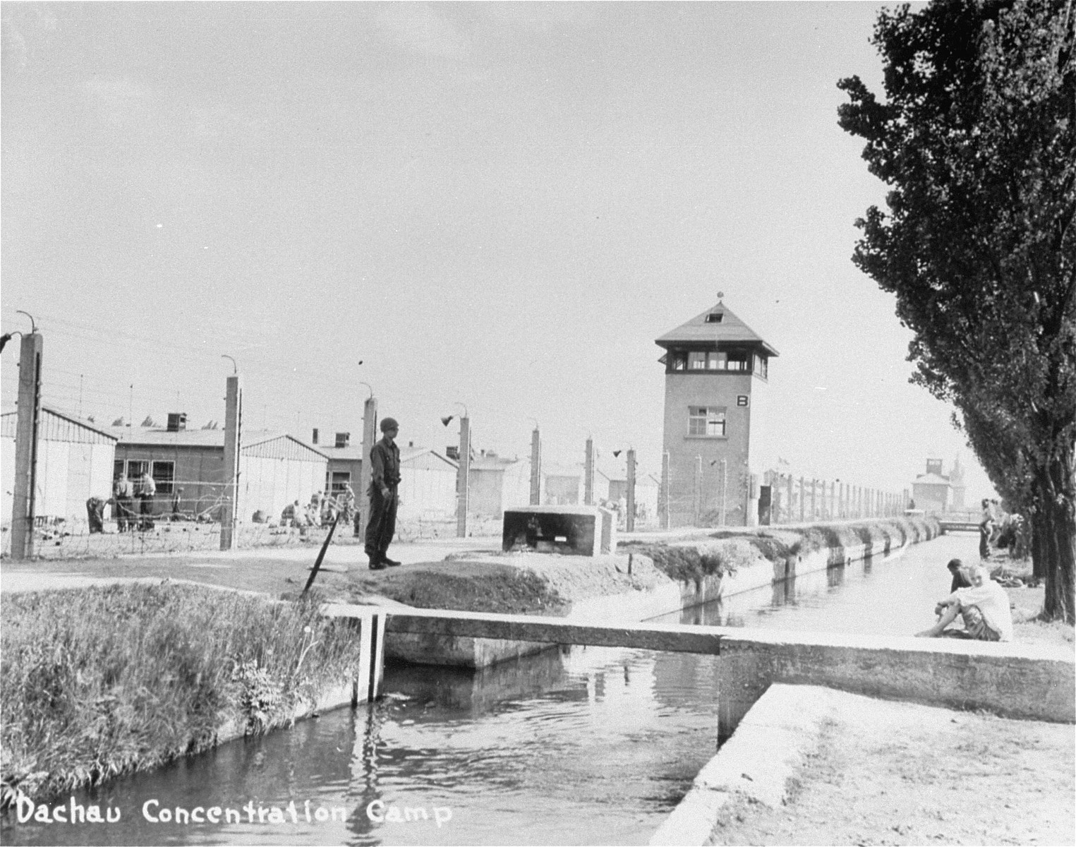 An American soldier stands guard outside of the Dachau concentration camp while survivors bathe in the moat.