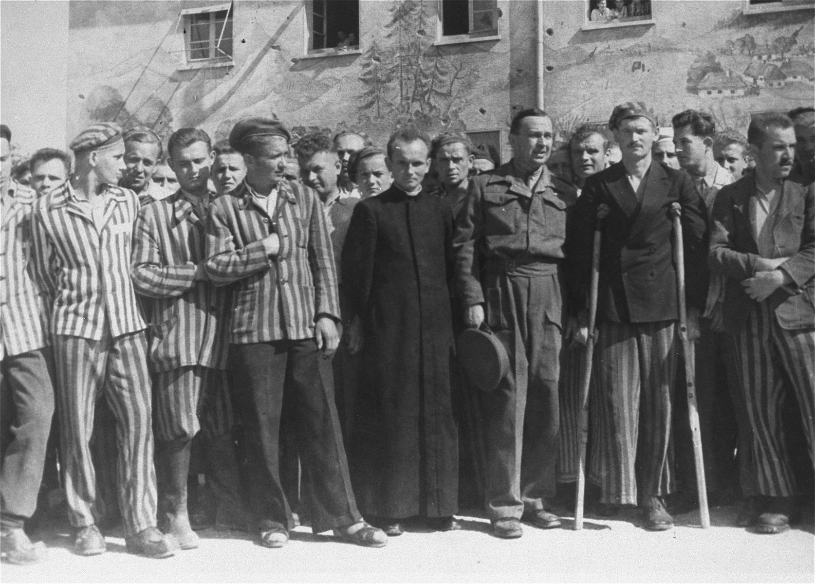 Major Edminson of UNRRA in Dachau with survivors his agency is aiding.  The priest next to him is a Pole and is one of the 150 survivors of 2500 Polish Roman Catholic priests who were incarcerated in Dachau.