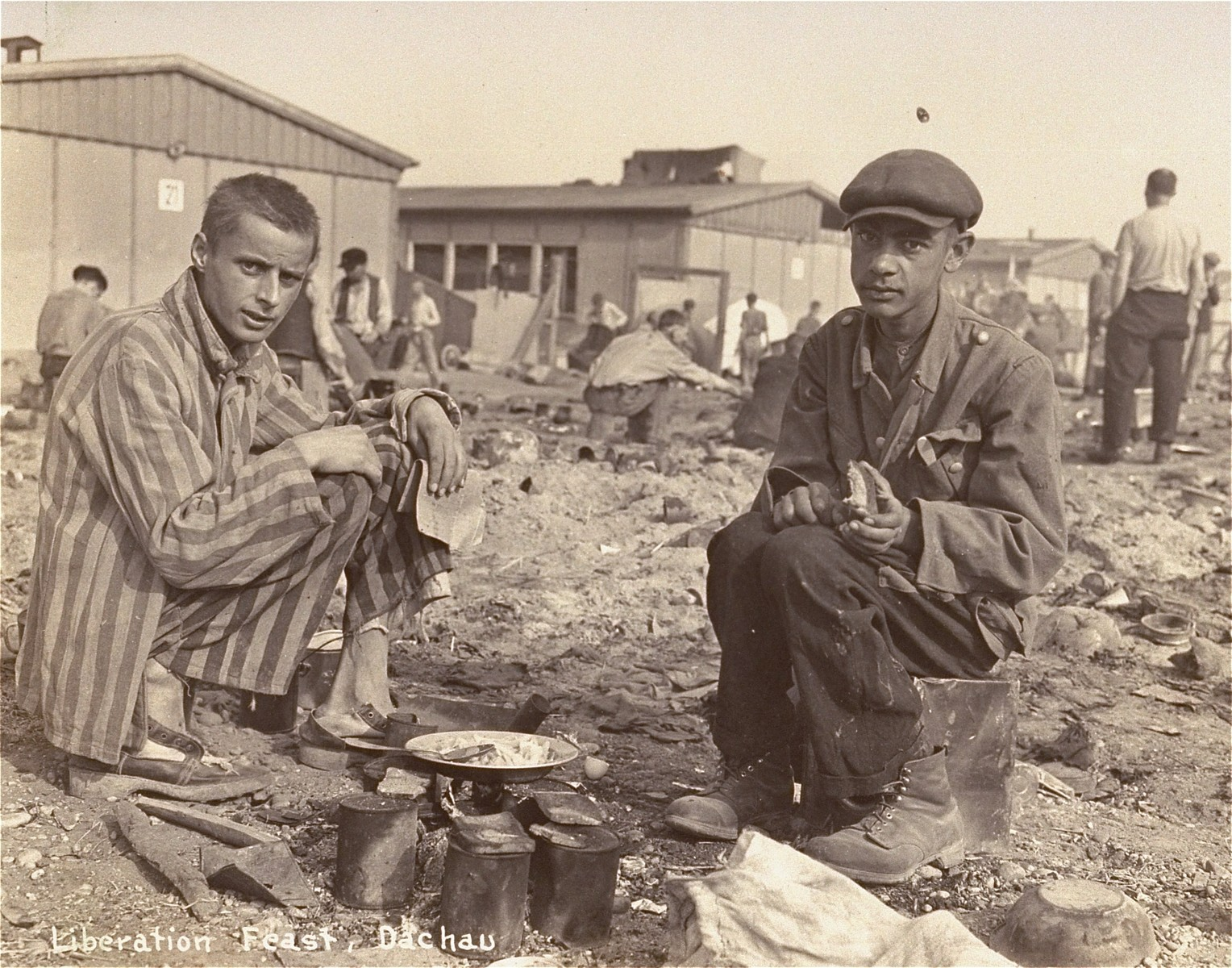 Two survivors prepare food outside the barracks.  The man on the right, presumably, is Jean (Johnny) Voste, born in Belgian Congo, who was the only black prisoner in Dachau.