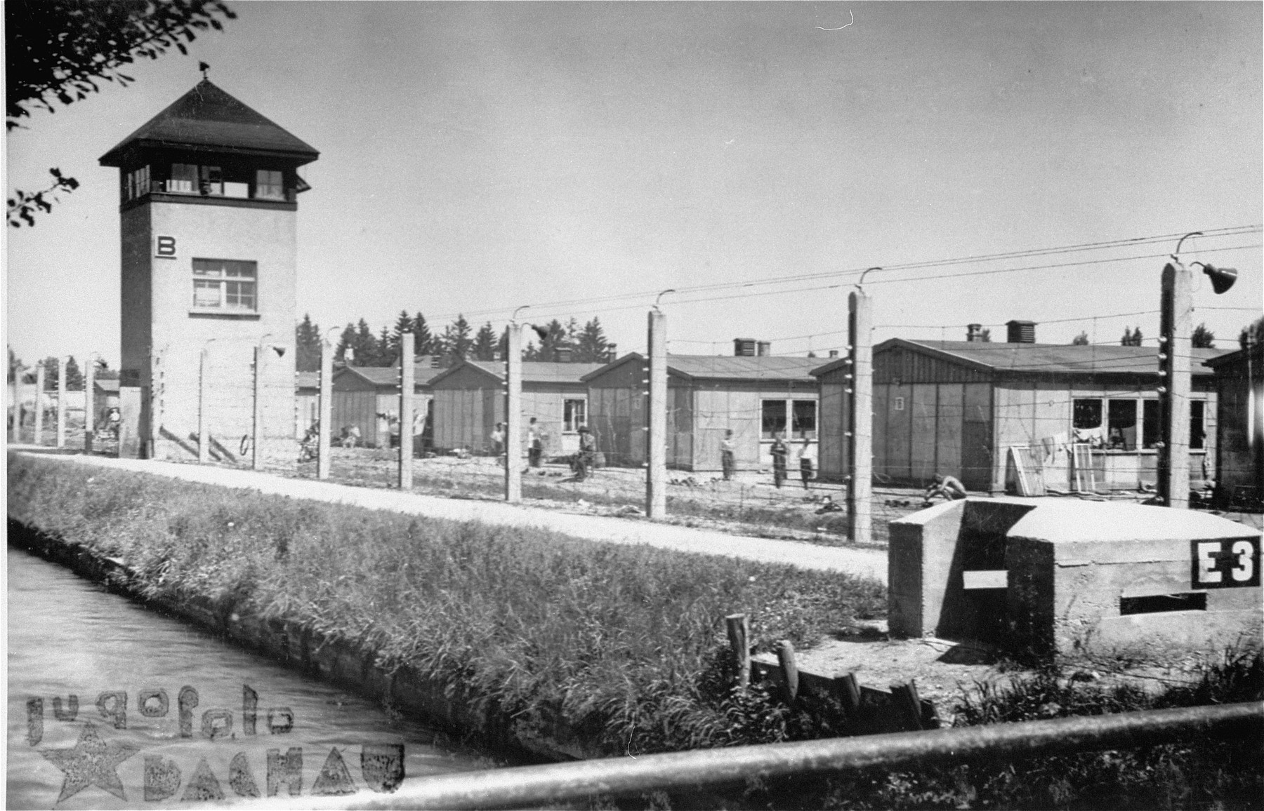 A view of the electrified barbed wire fence, the moat and the watch tower in Dachau.