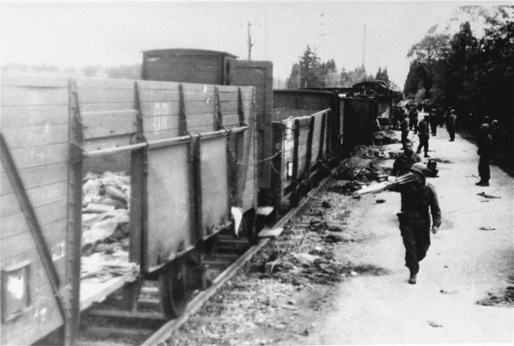 American soldiers, including a photographer carrying a camera and tripod, view the Dachau death train.