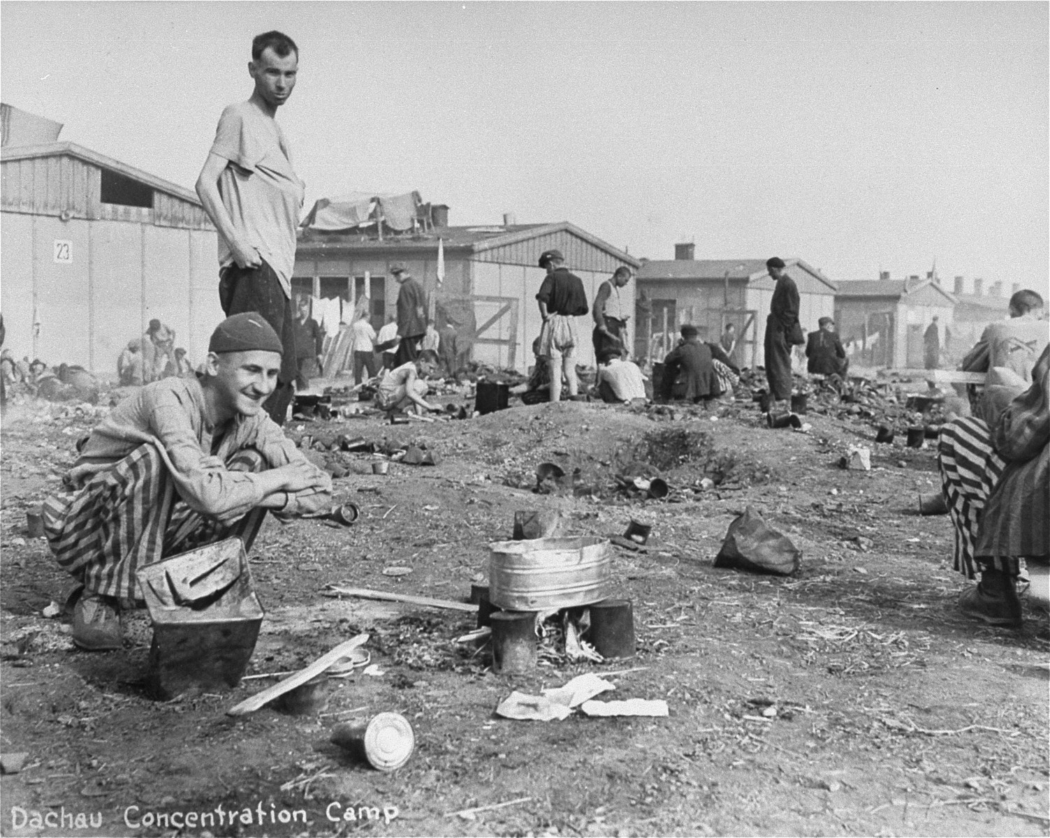 Survivors in Dachau cooking food over open fire.