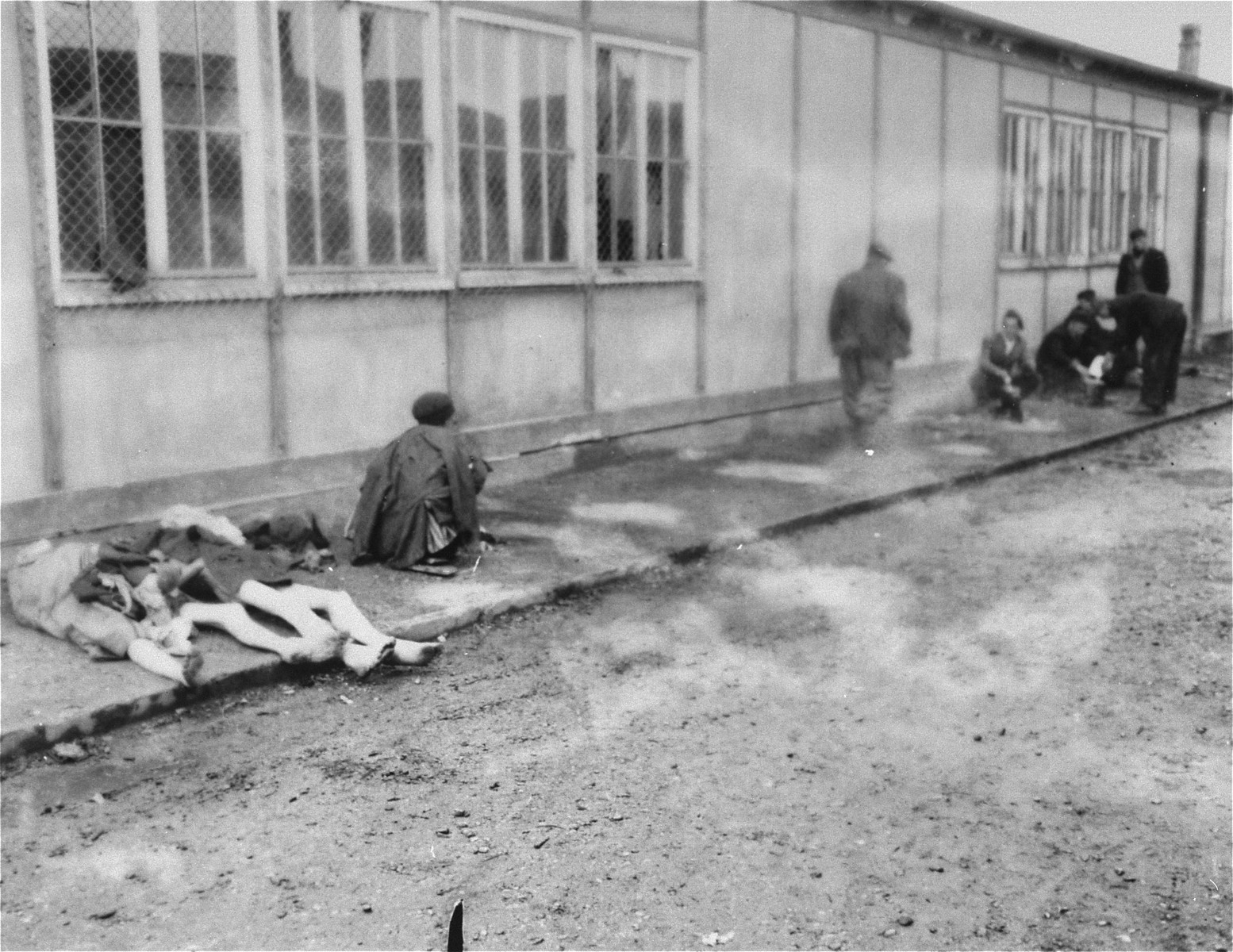 Survivors and corpses outside of a barracks in Dachau.