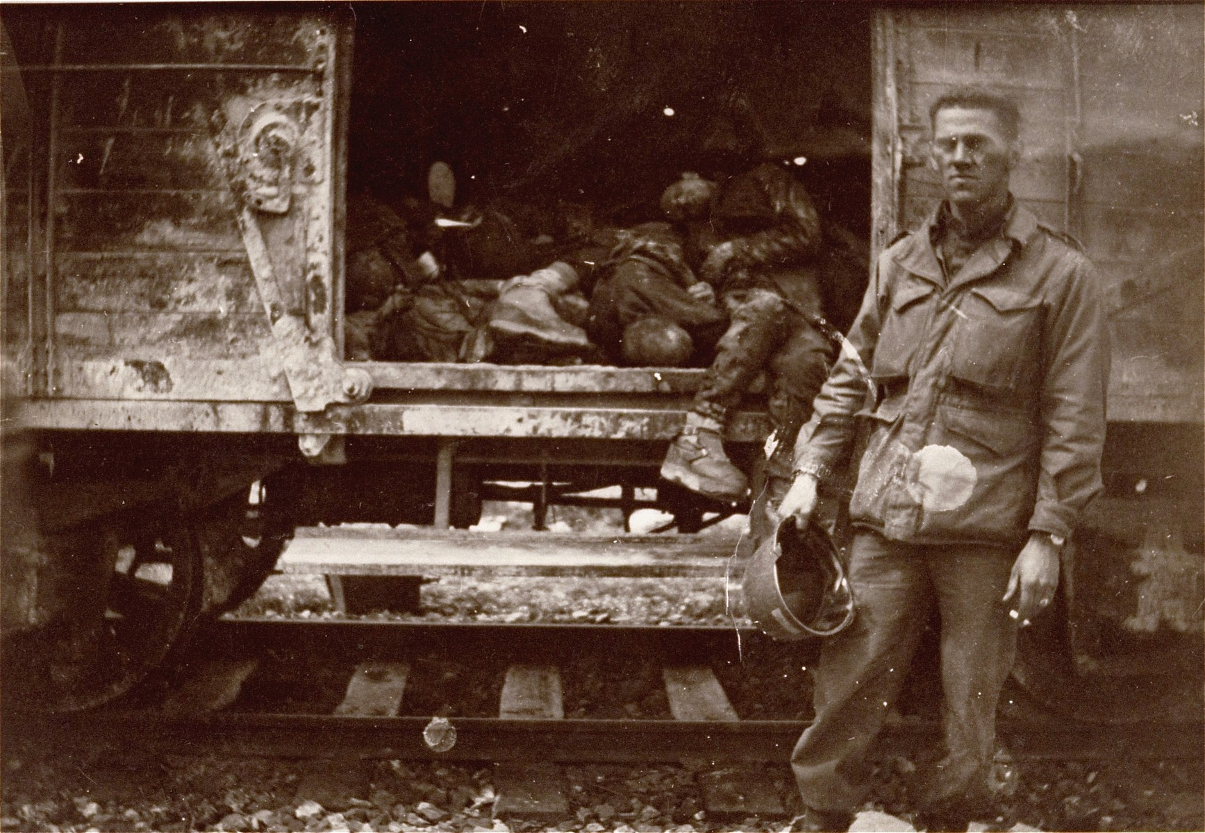 An American soldier poses next to one of the open railcars of the Dachau death train.