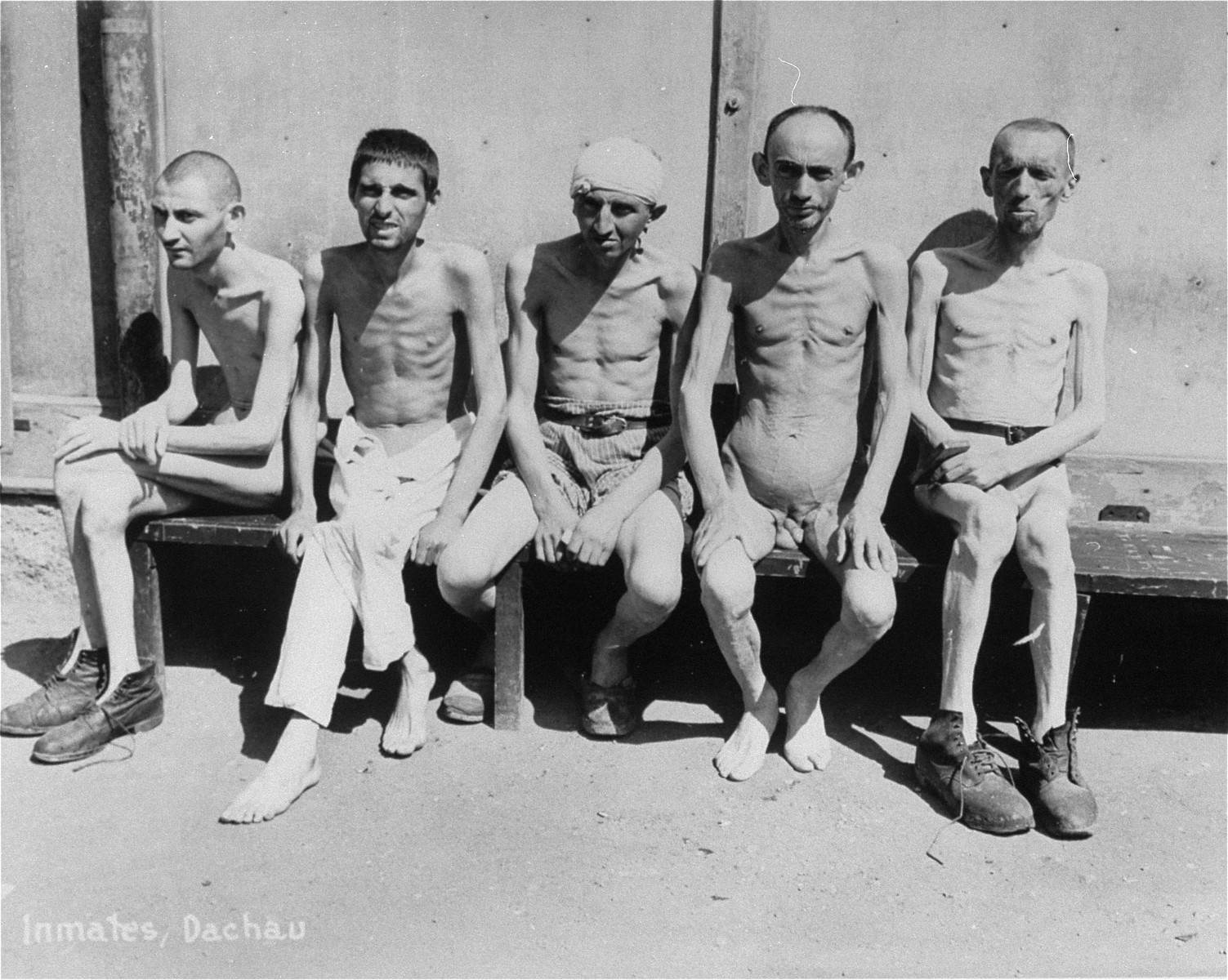 Survivors in Dachau sit together on a bench.