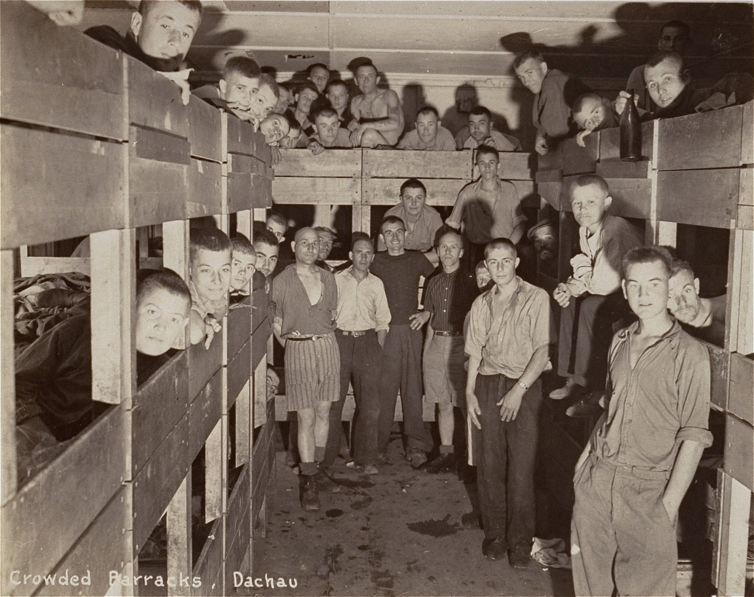 Survivors in a crowded Dachau barrack after liberation.