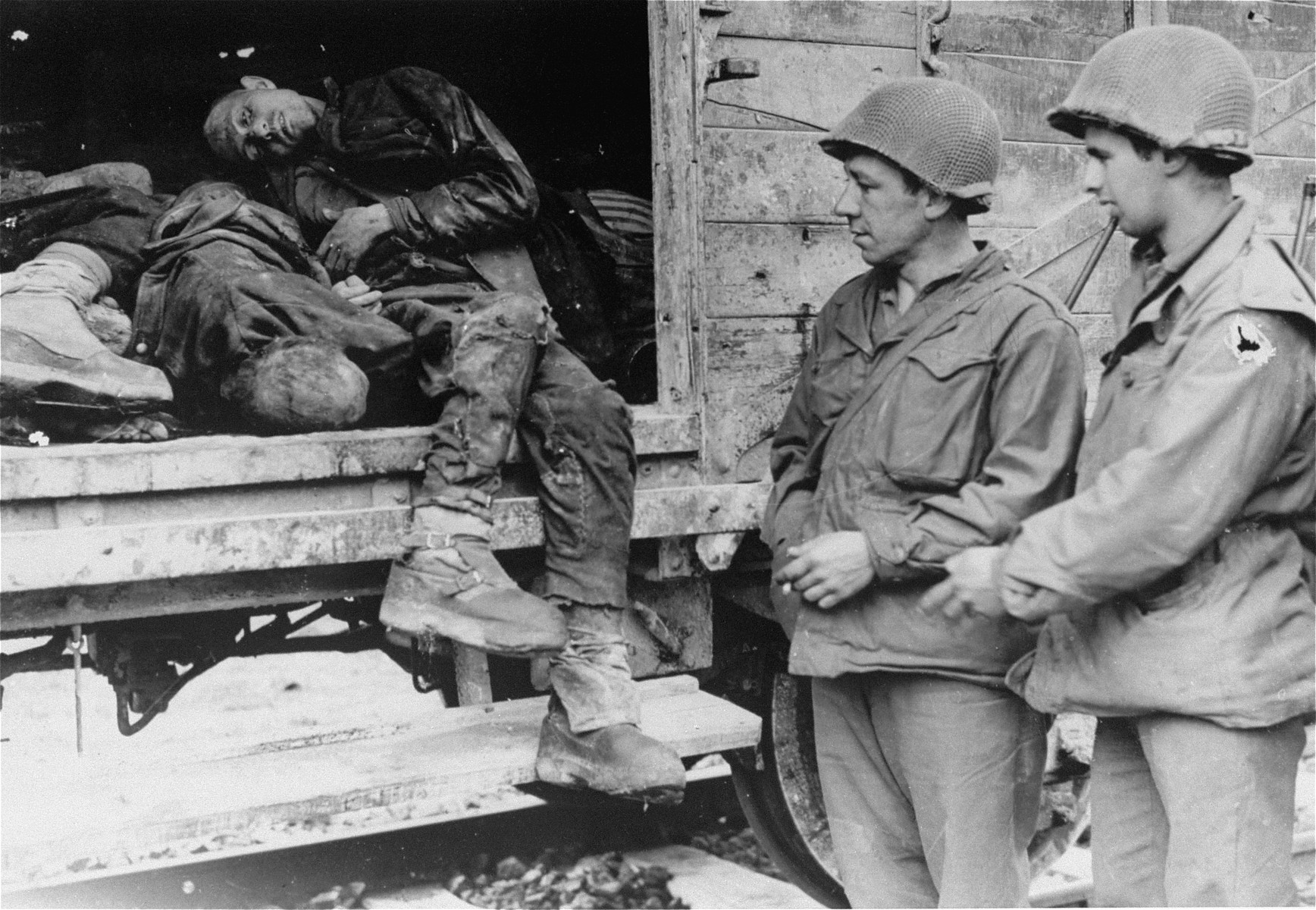 American soldiers view the bodies in one of the open railcars of the Dachau death train.