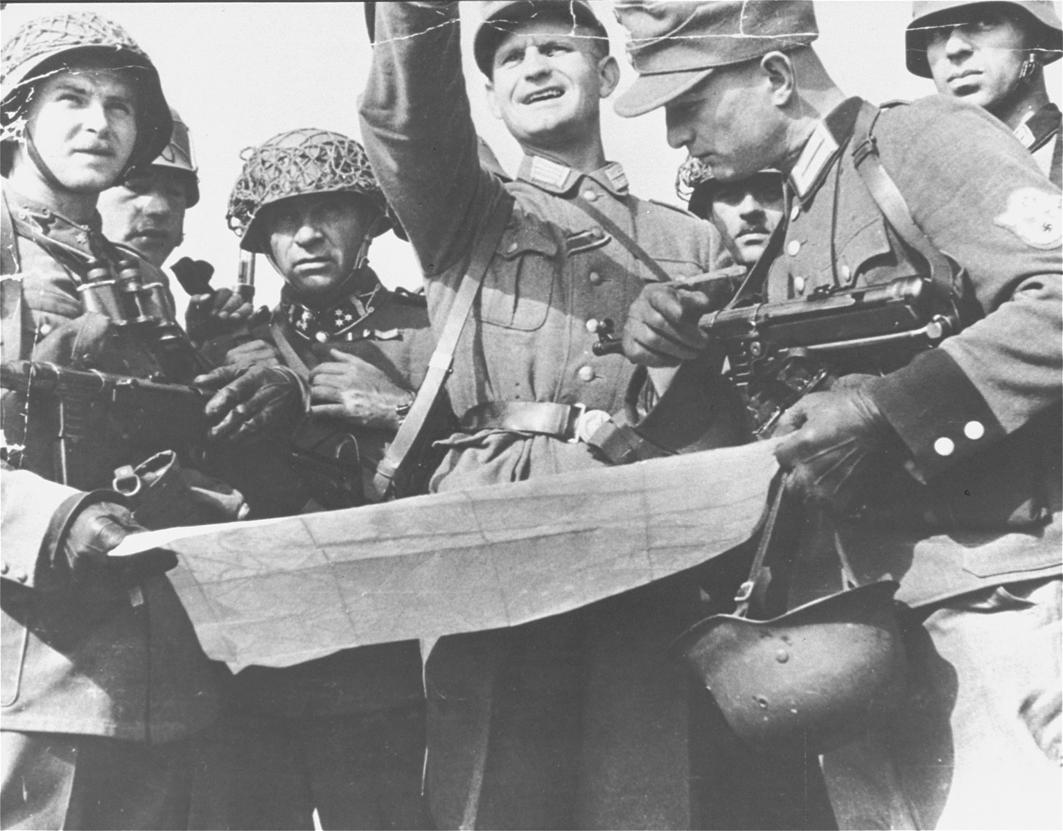 German and Hungarian soldiers consult a map during a military operation.    The man on the right is a German police officer.