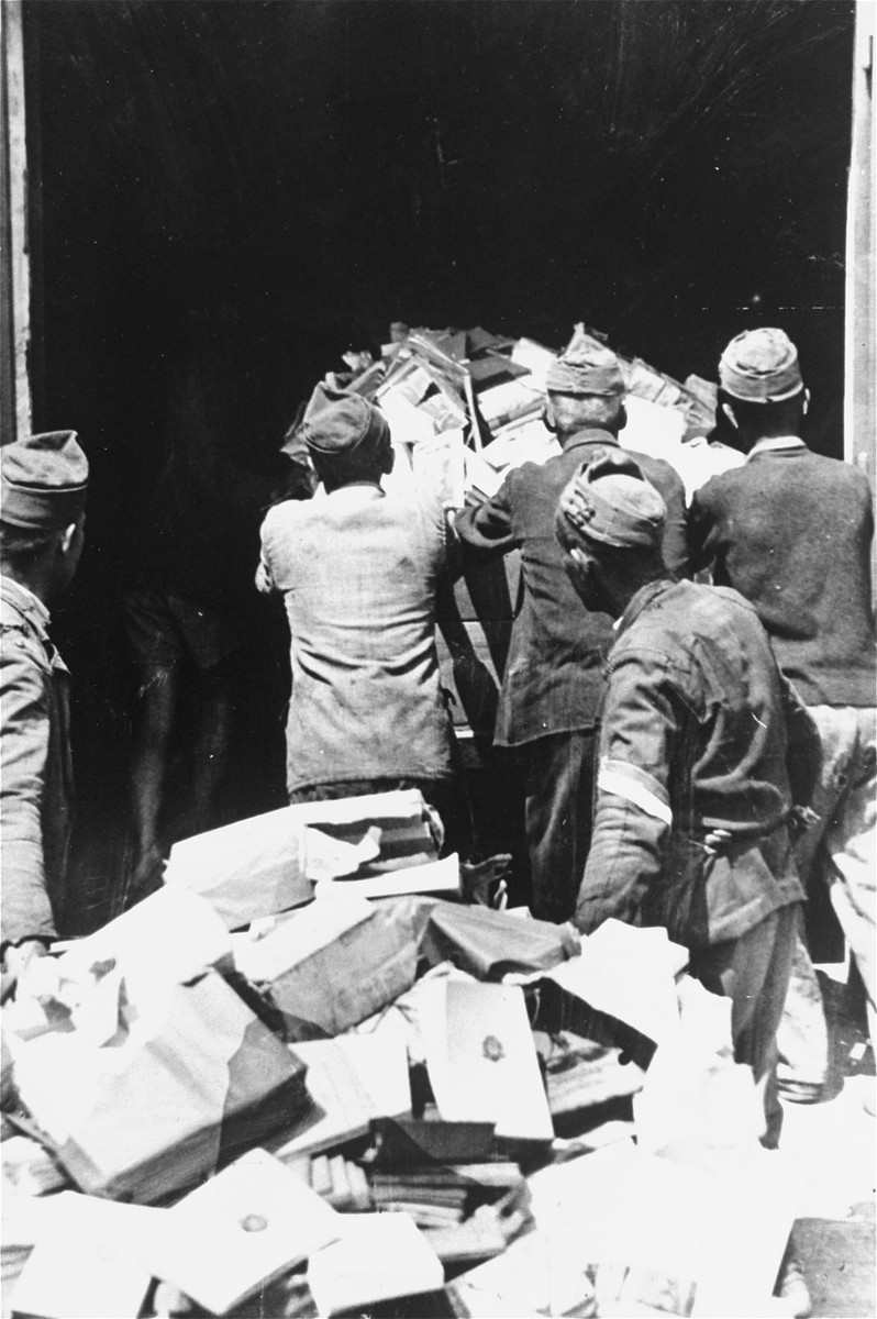 Hungarian workers, including Jews in the labor service, wheel a cart laden with books written by Jews into a paper mill where they will be destroyed.