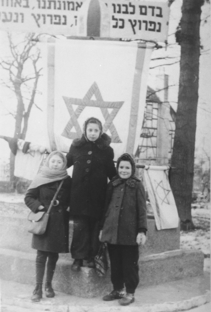 Three girls stand in front of Zionist flags in the Babenhausen displaced persons' camp.  Sylwia Laufer is on the right and Pola Kandel is on the left.